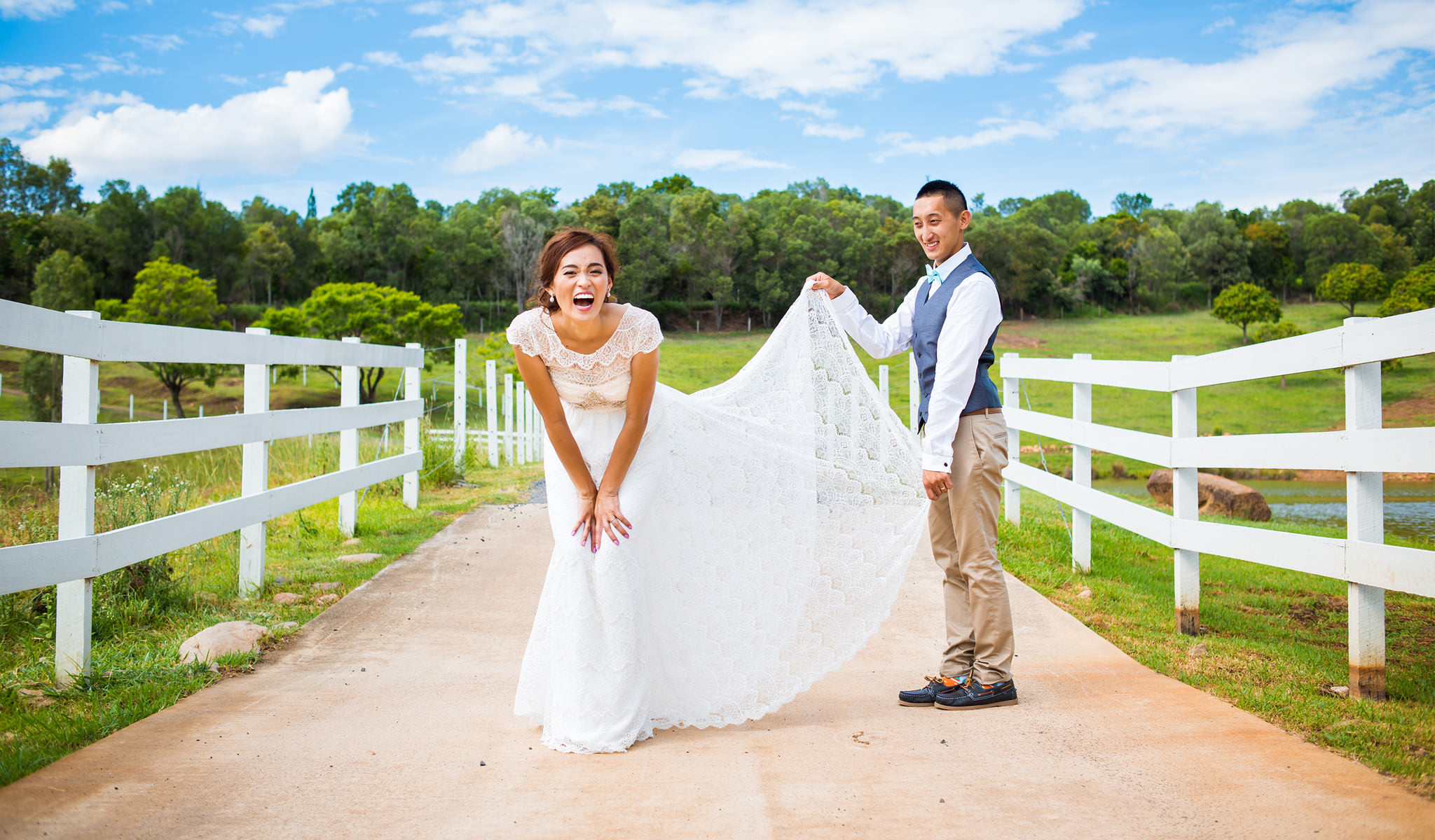 Groom lifting up bride's dress while she laughs