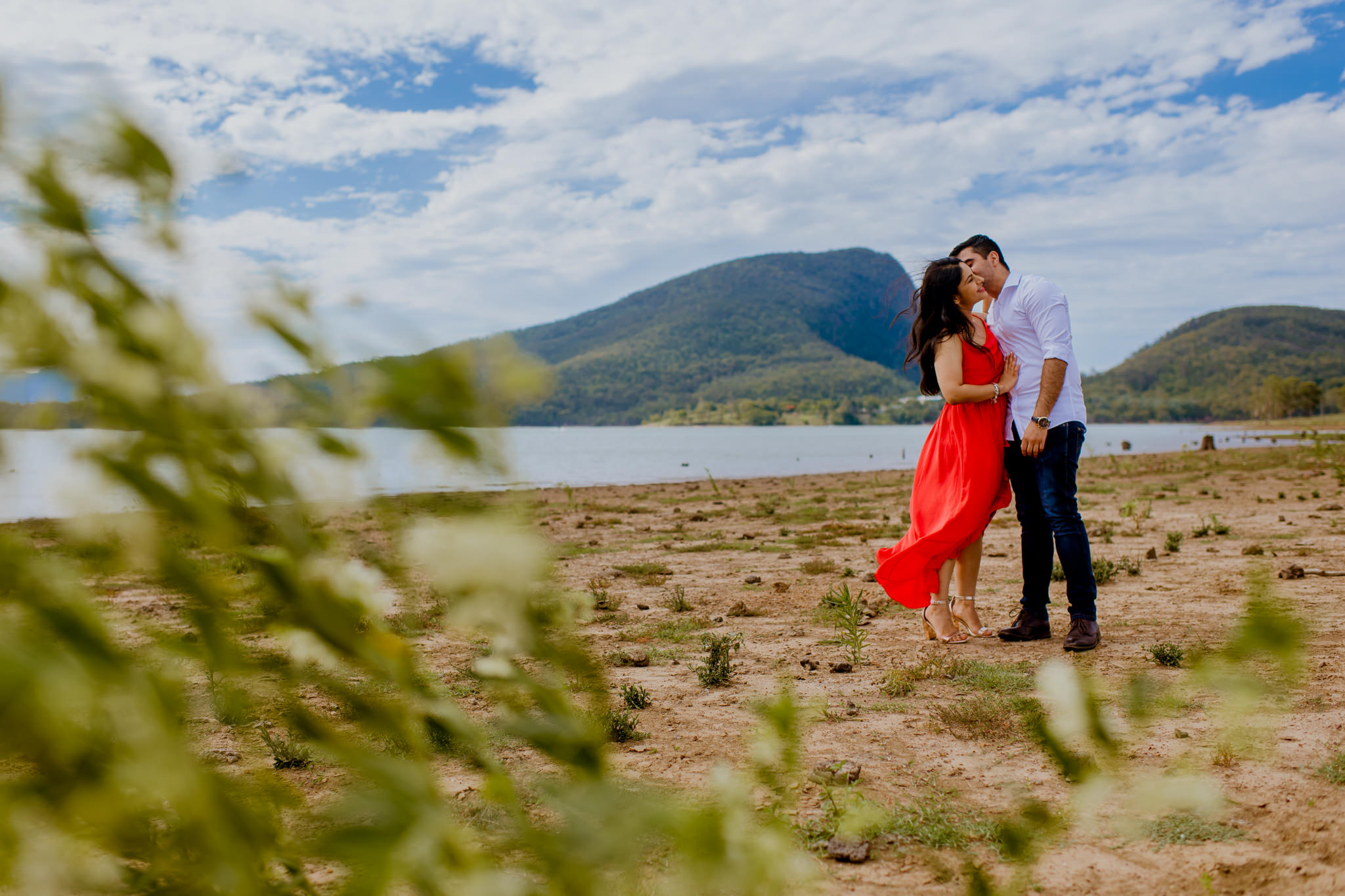 Indian couple hugging on shore beside lake with mountainous landscape in background