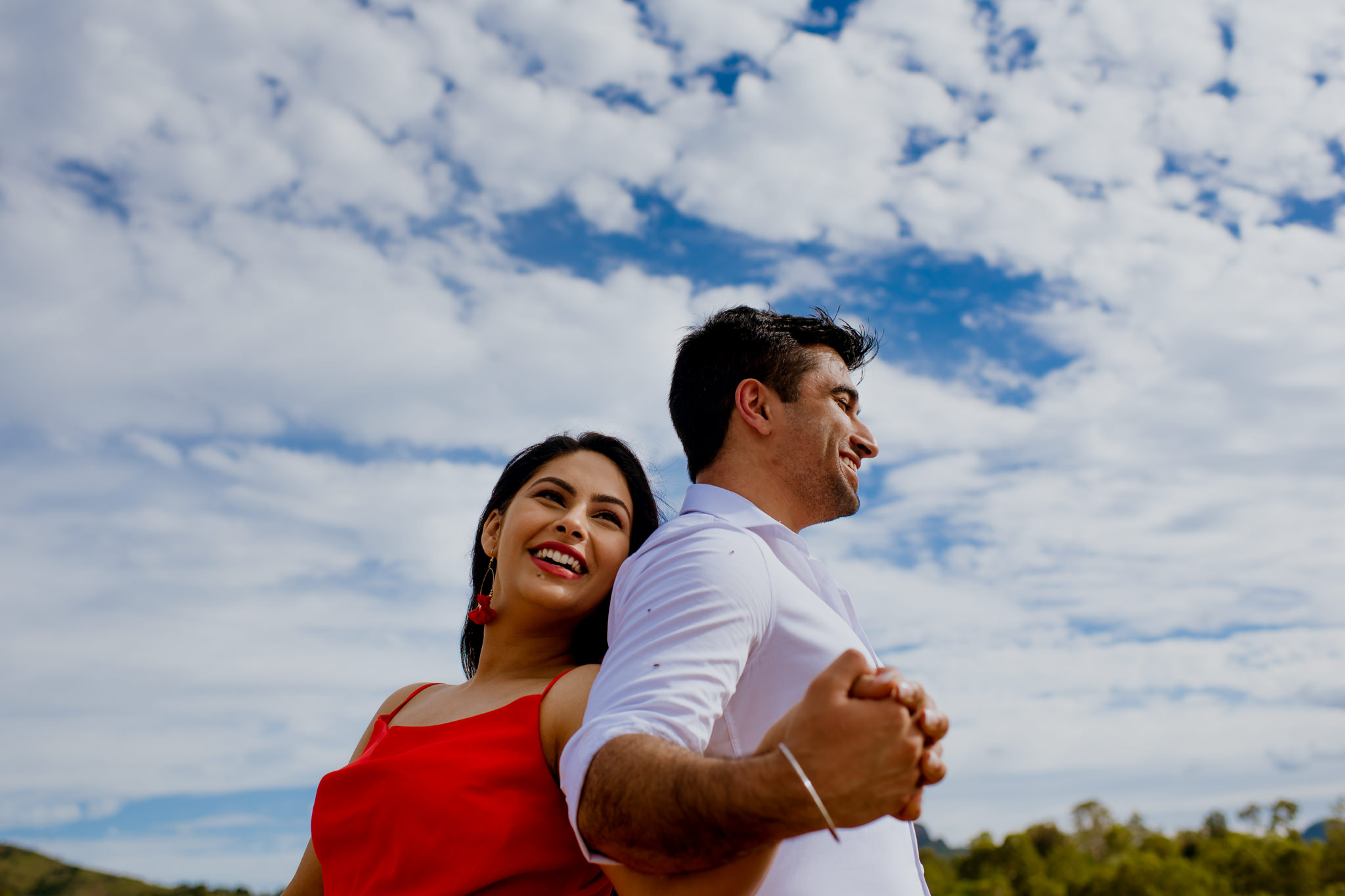 Couple holding hands and standing back to back with a cloudy blue sky above them