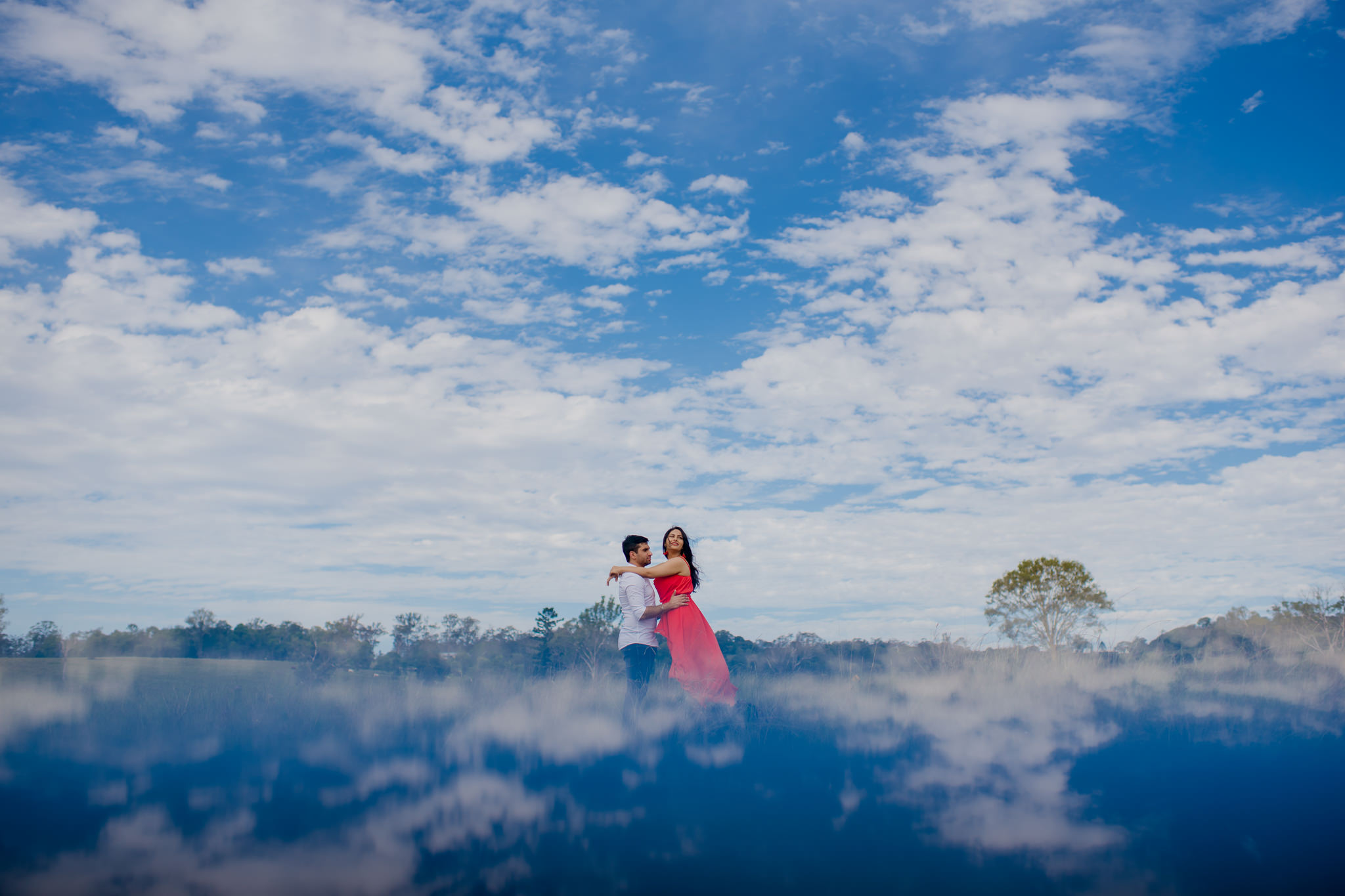 Couple posing romantically with a cloudy blue sky behind them and reflected on the bottom