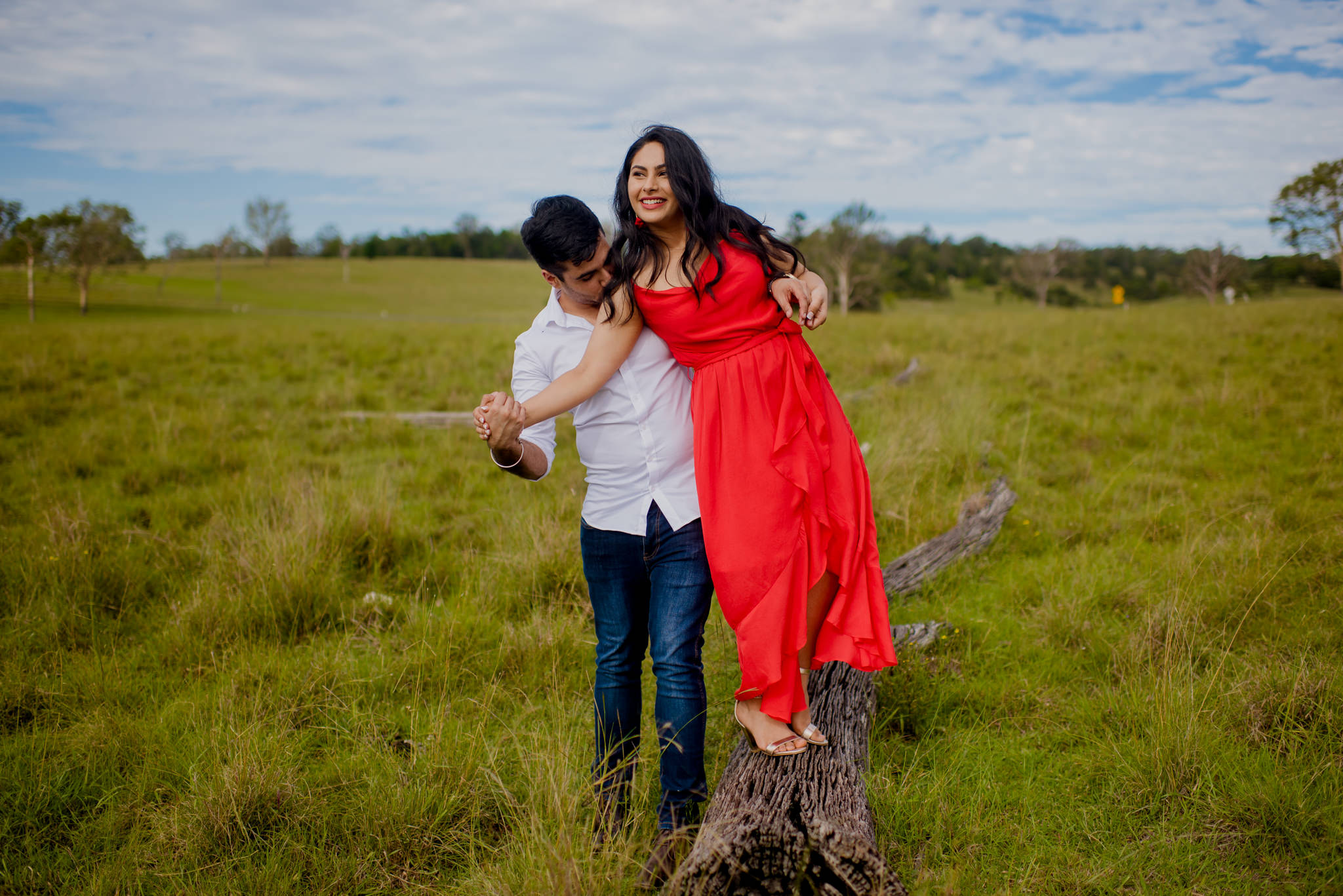 Boy holds his girlfriends hand and kisses her arm as he helps her walk across a fallen log in a grassy field