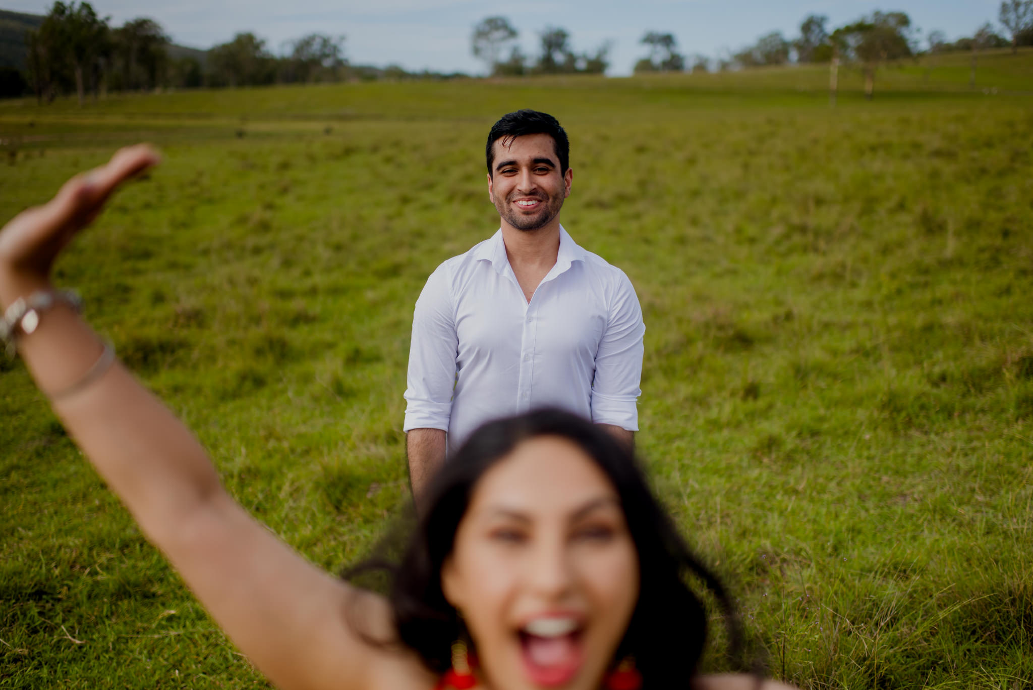 Boy laughs as his girlfriend photobombs the photo in the foreground