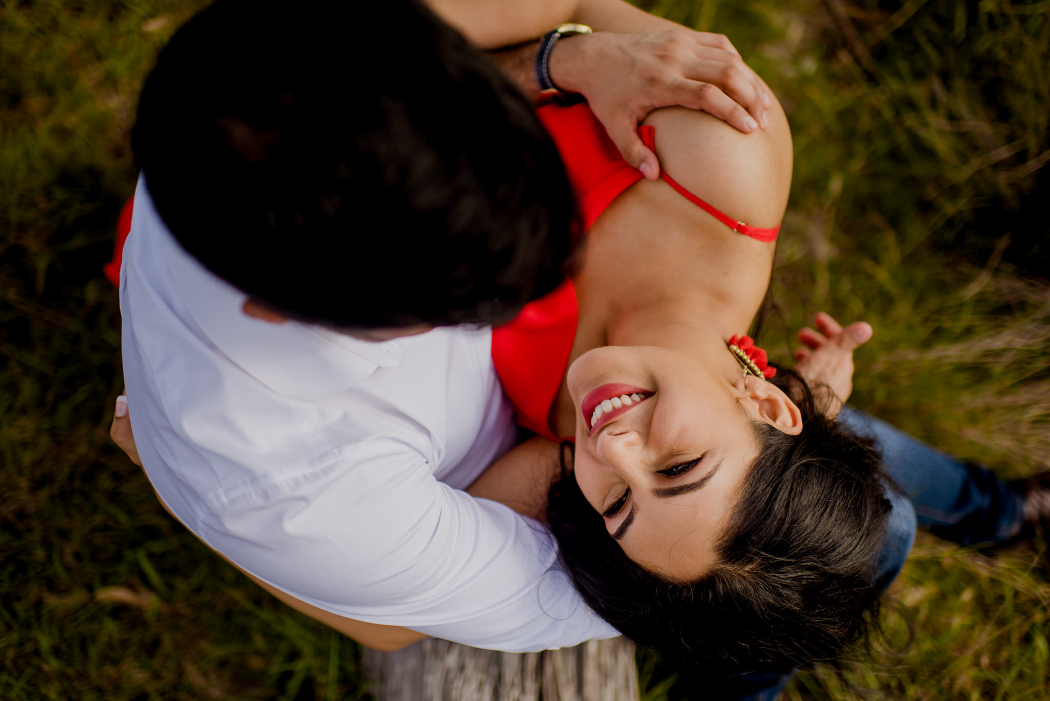 Bird's eye view of girl in red dress lying on boy's lap and looking up lovingly
