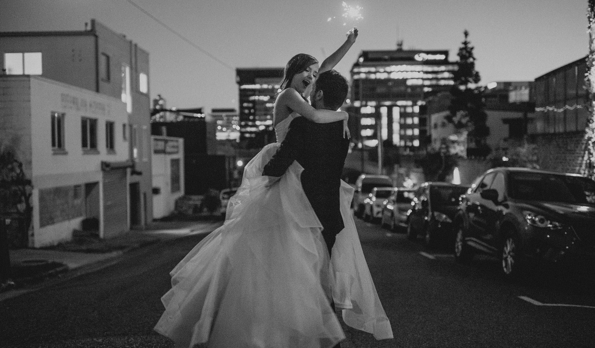 Happy bride with sparkler being lifted by groom