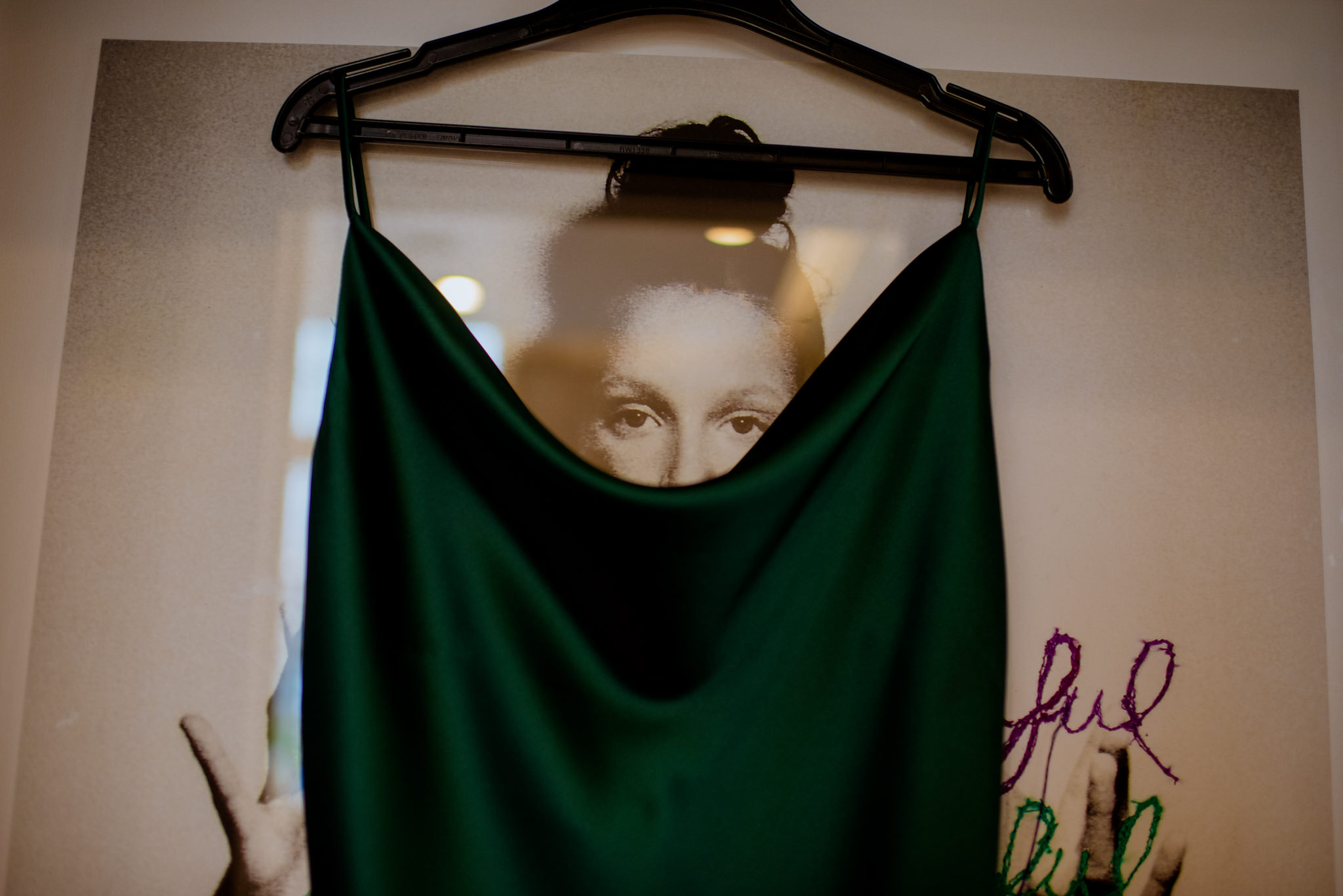 Green dress hanging in front of portrait of lady