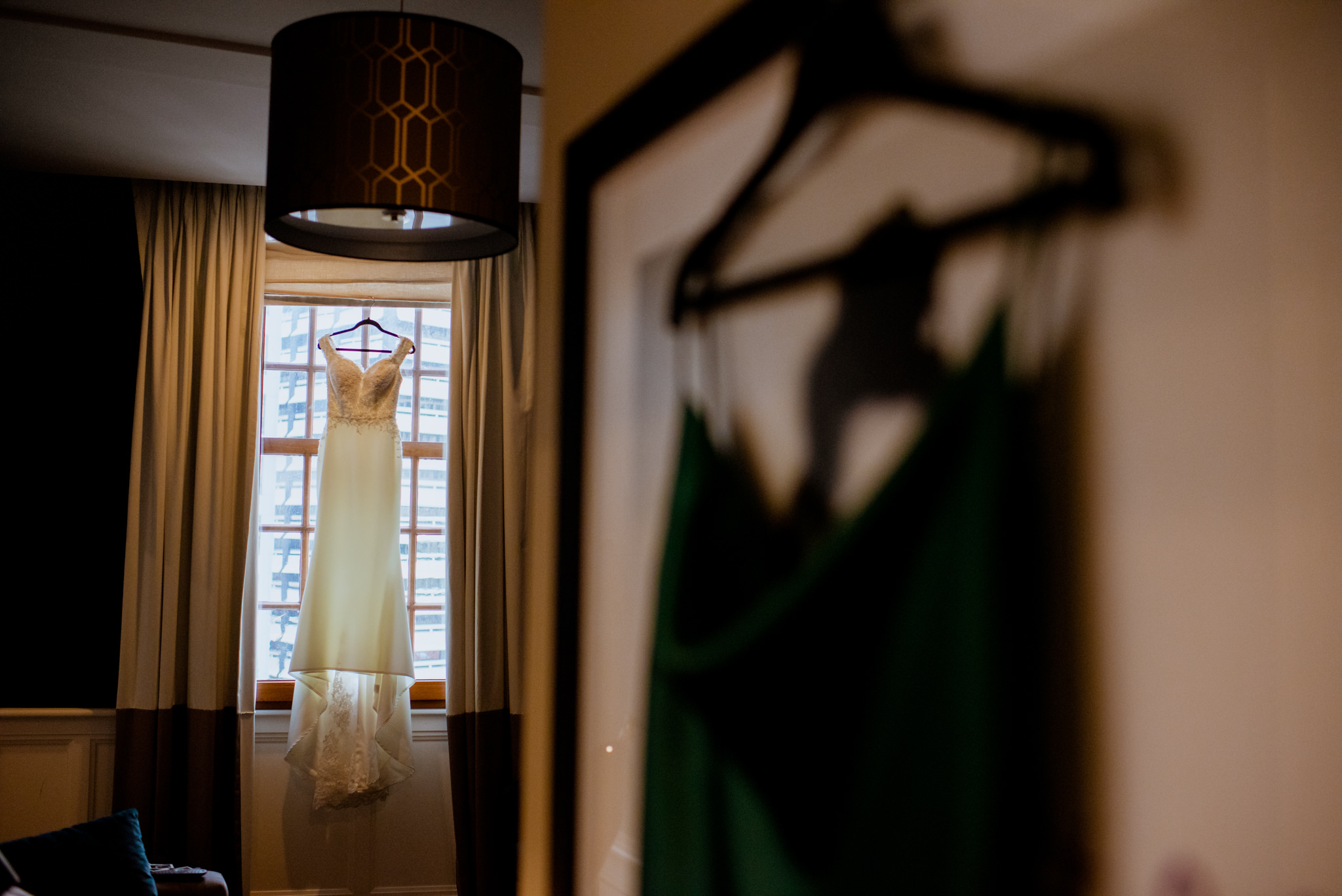 Wedding dress hung in window in background and green dress hung in foreground