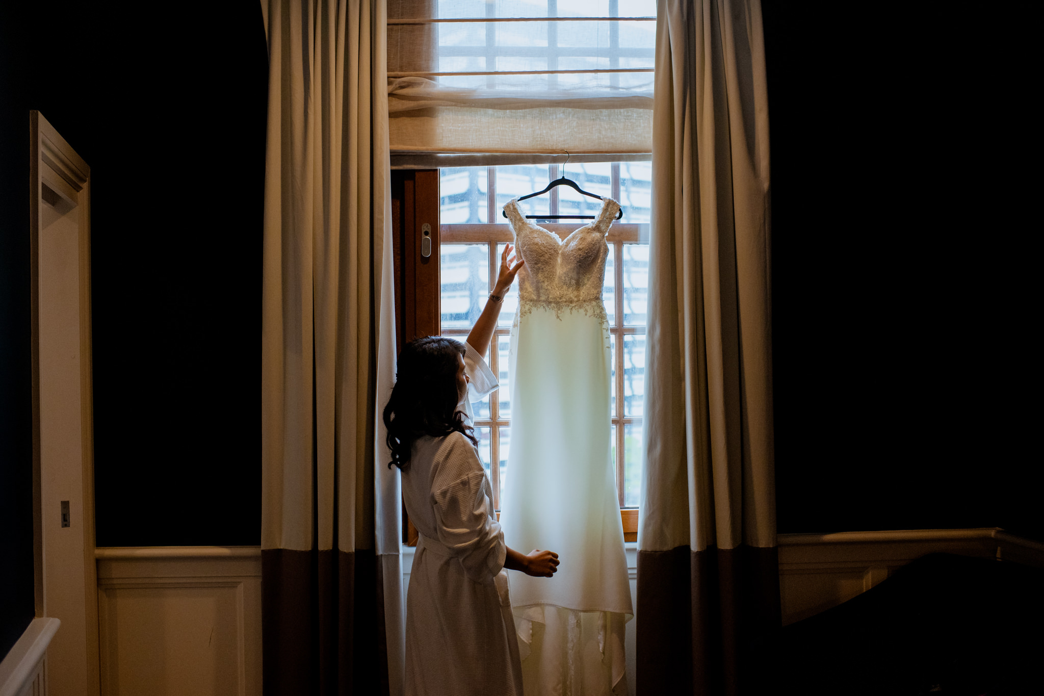 Girl in bathrobe adjusting wedding dress hanging in the windowsill