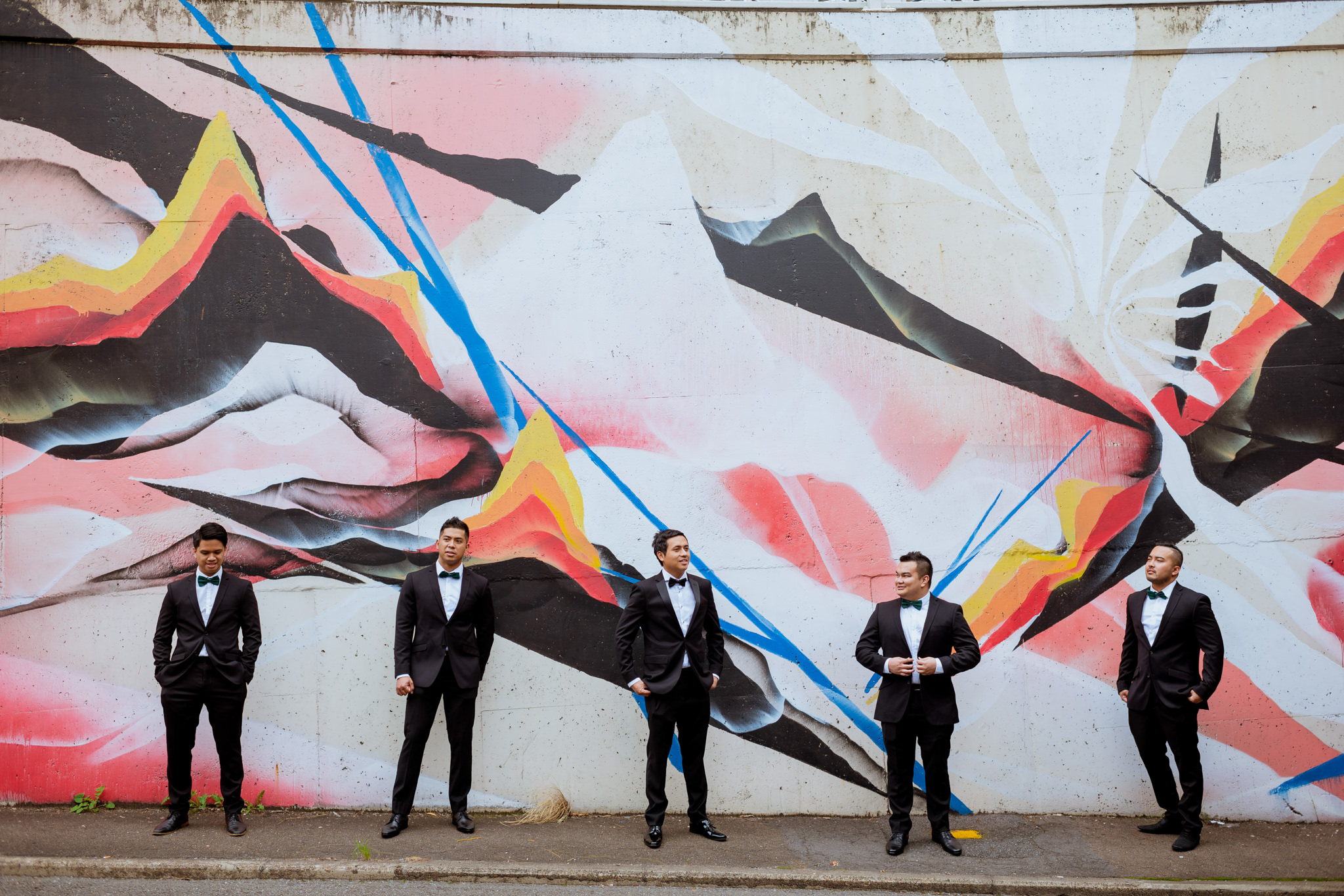 Groom and groomsmen posing in front of large graffiti wall