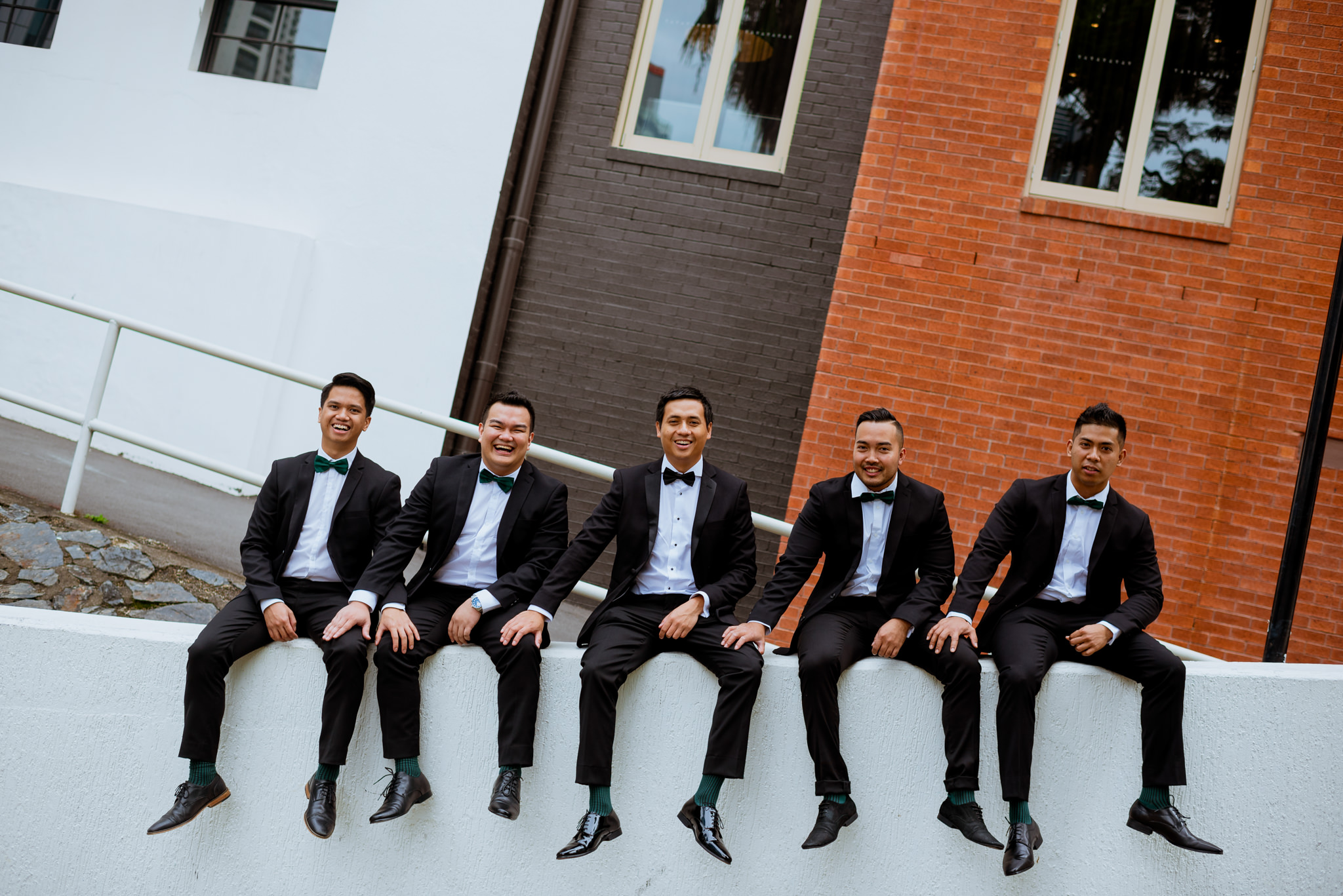 Groom and groomsmen sitting on slanted wall, touching each other's knees