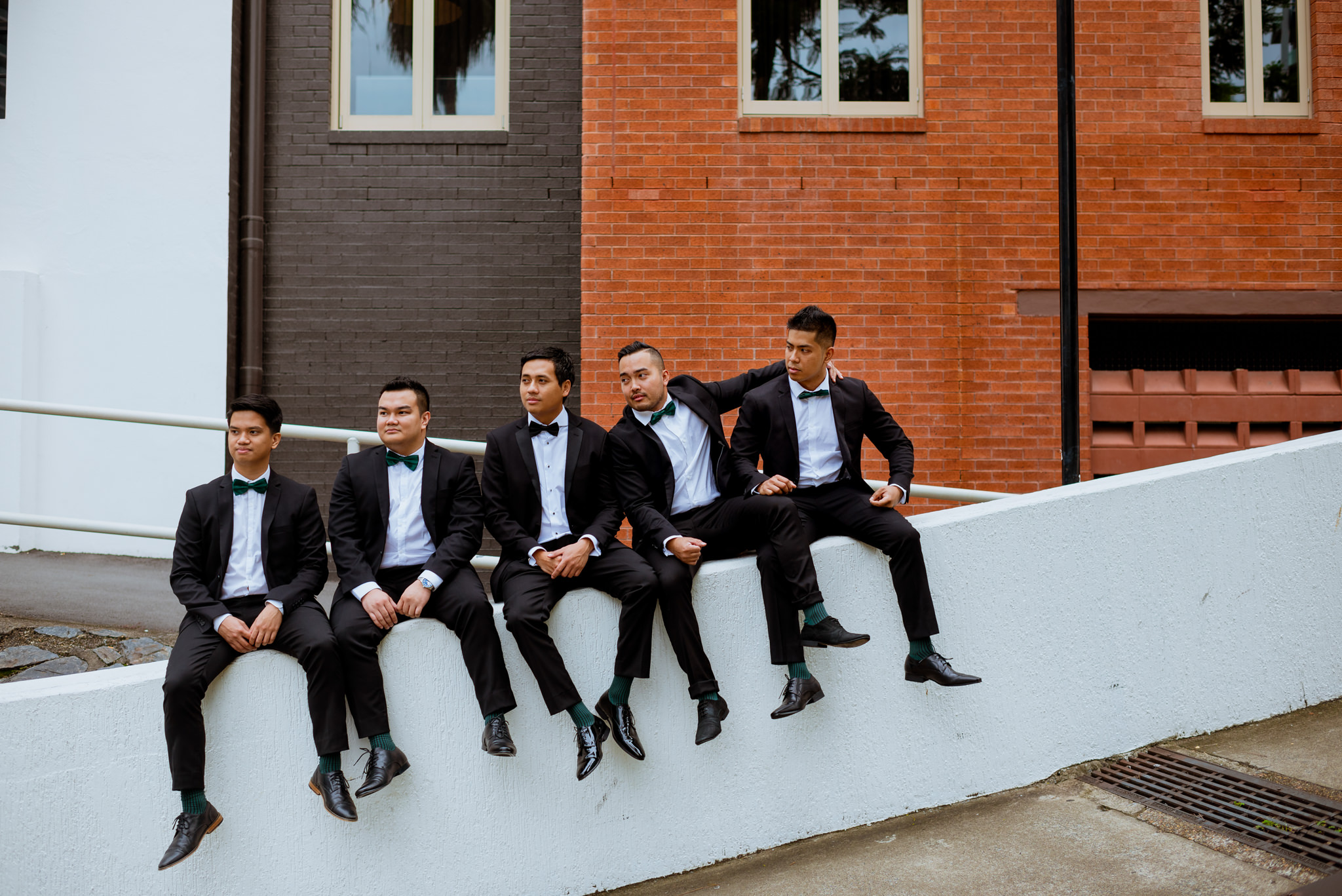 Groom and groomsmen sitting and posing on slanted wall in front of brick walls