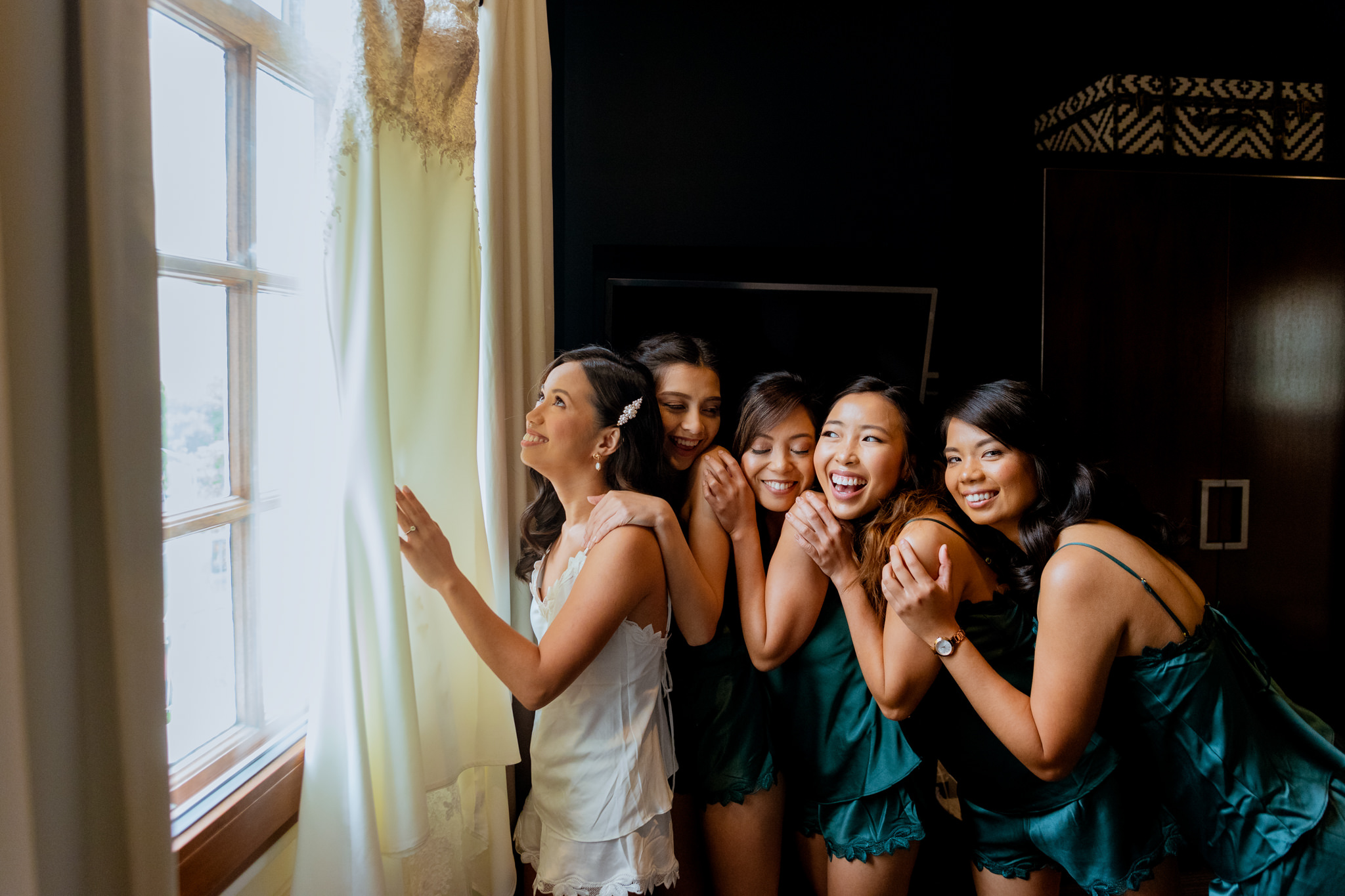 Bride admiring her dress in windowsill whilst bridesmaids playfully hug her from behind