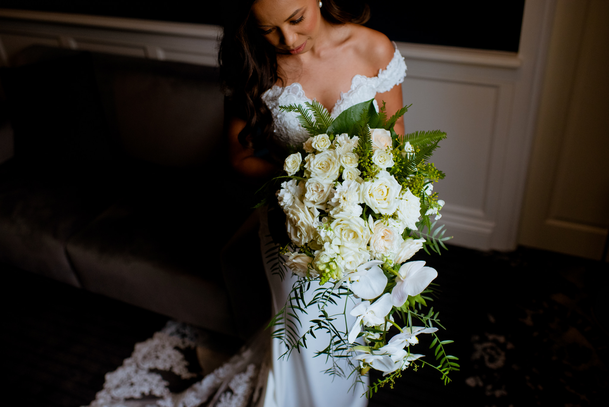 Bride stands and admires her large white wedding bouquet