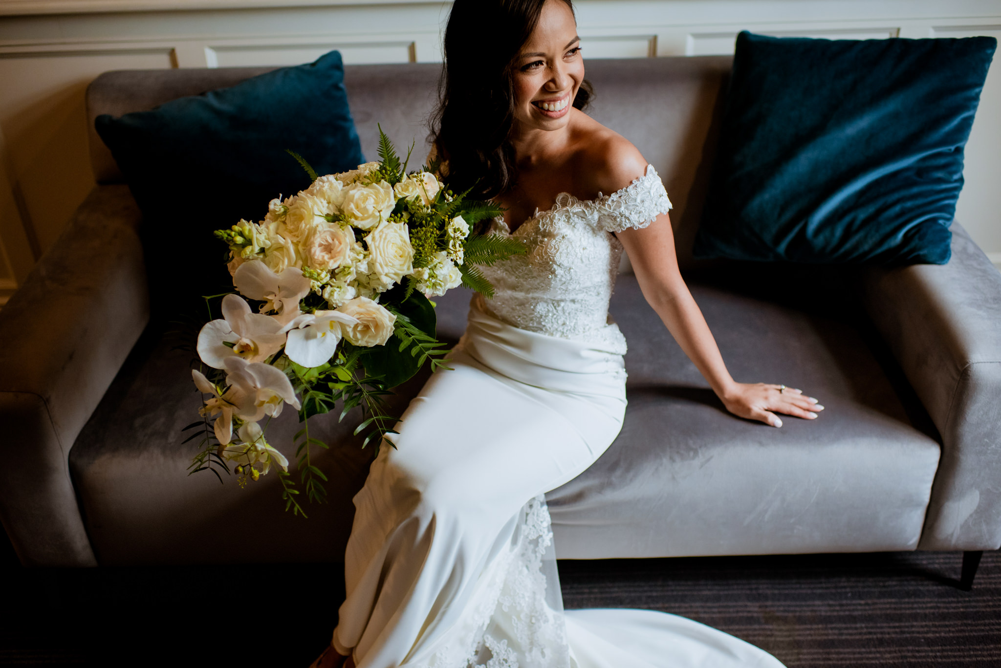 Bride sits on couch and laughs while posing with her wedding bouquet
