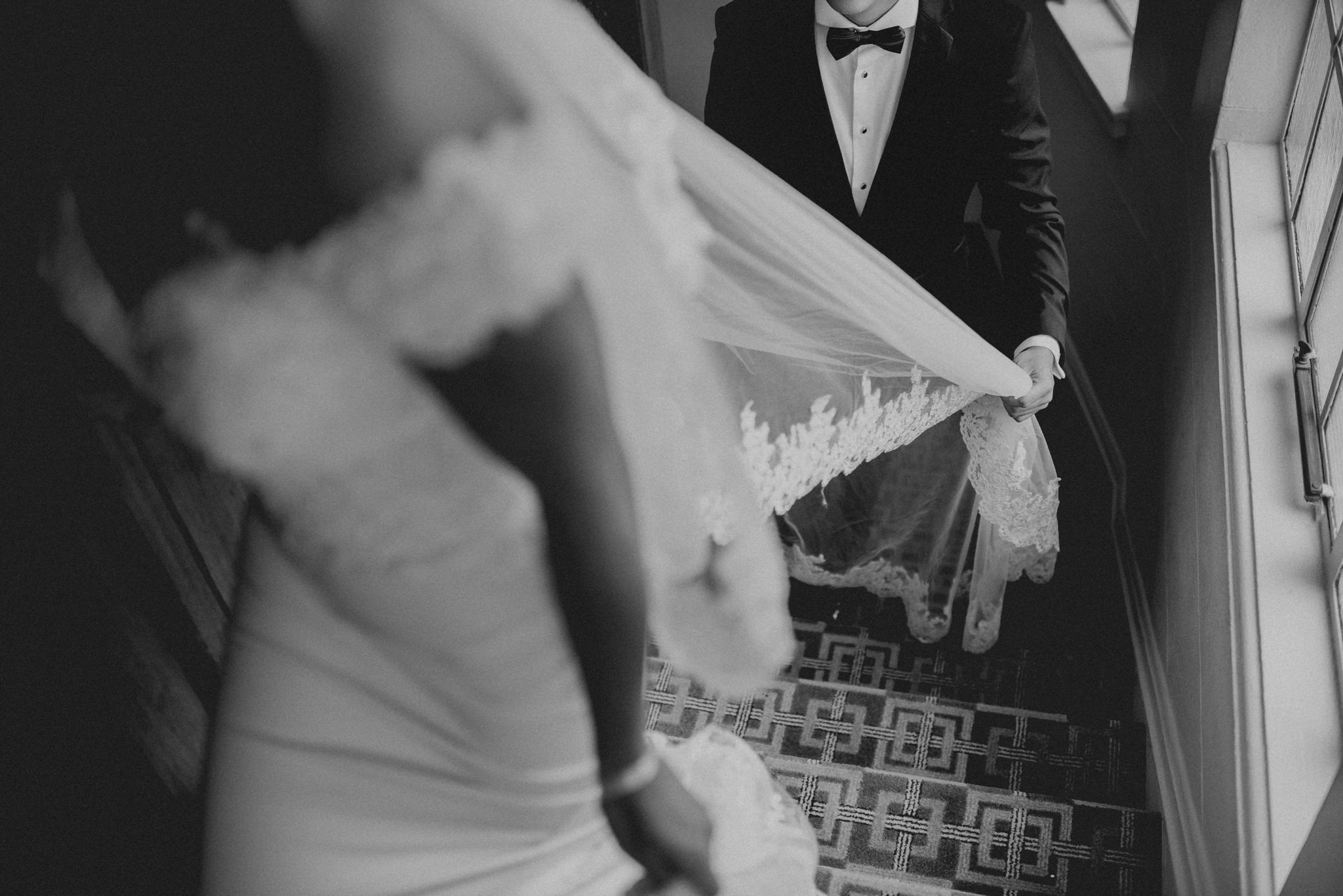 Groom holding his bride's wedding veil as she walks up stairs