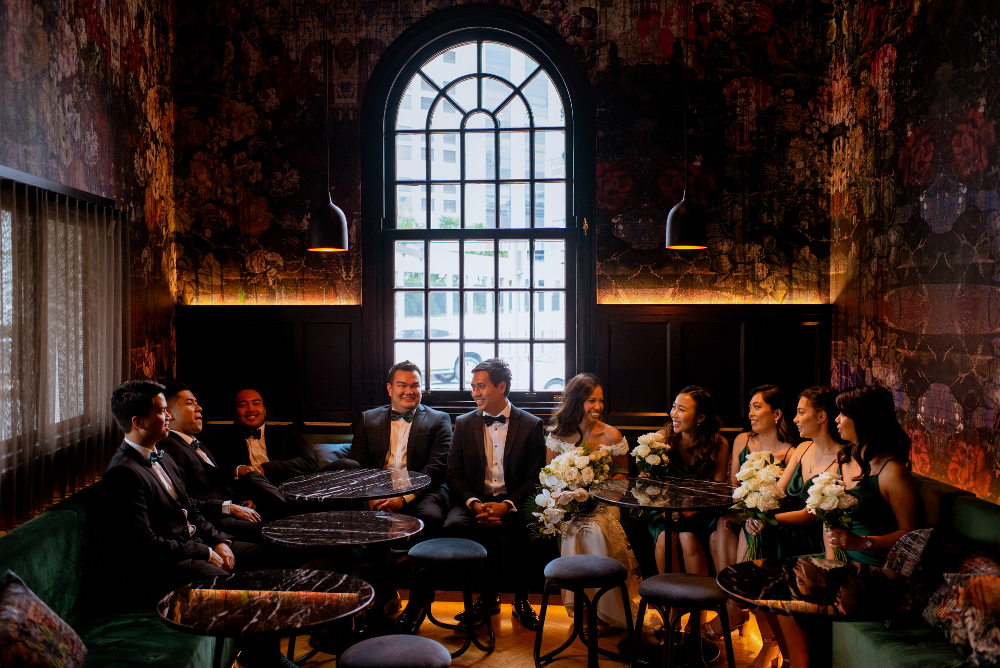 Bridal party casually sits in warmly lit vintage style bar