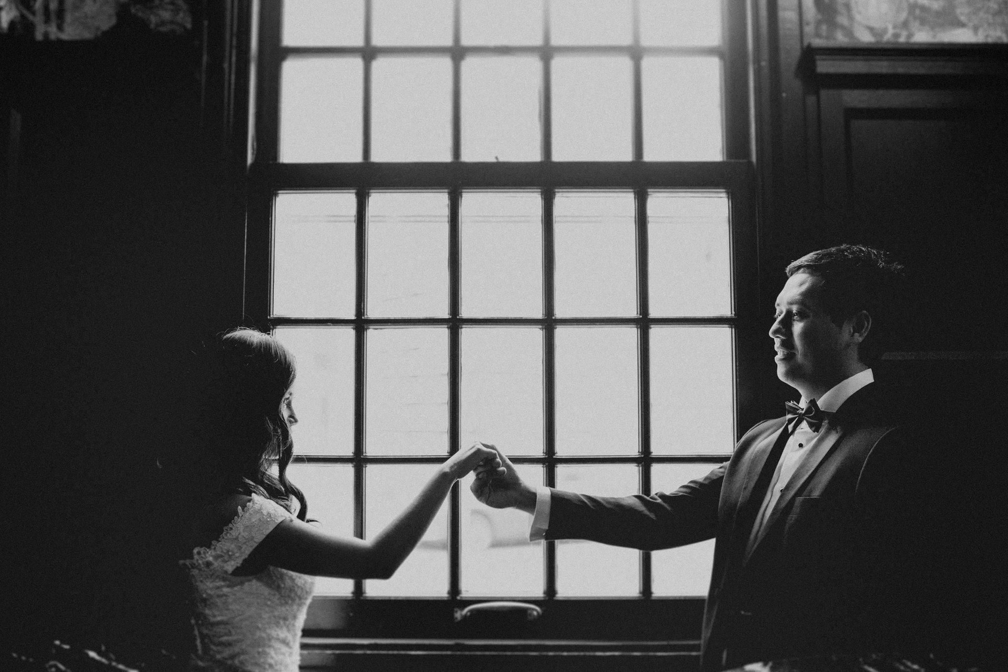 Bride and groom stand in front of a bright window and playfully hold handss