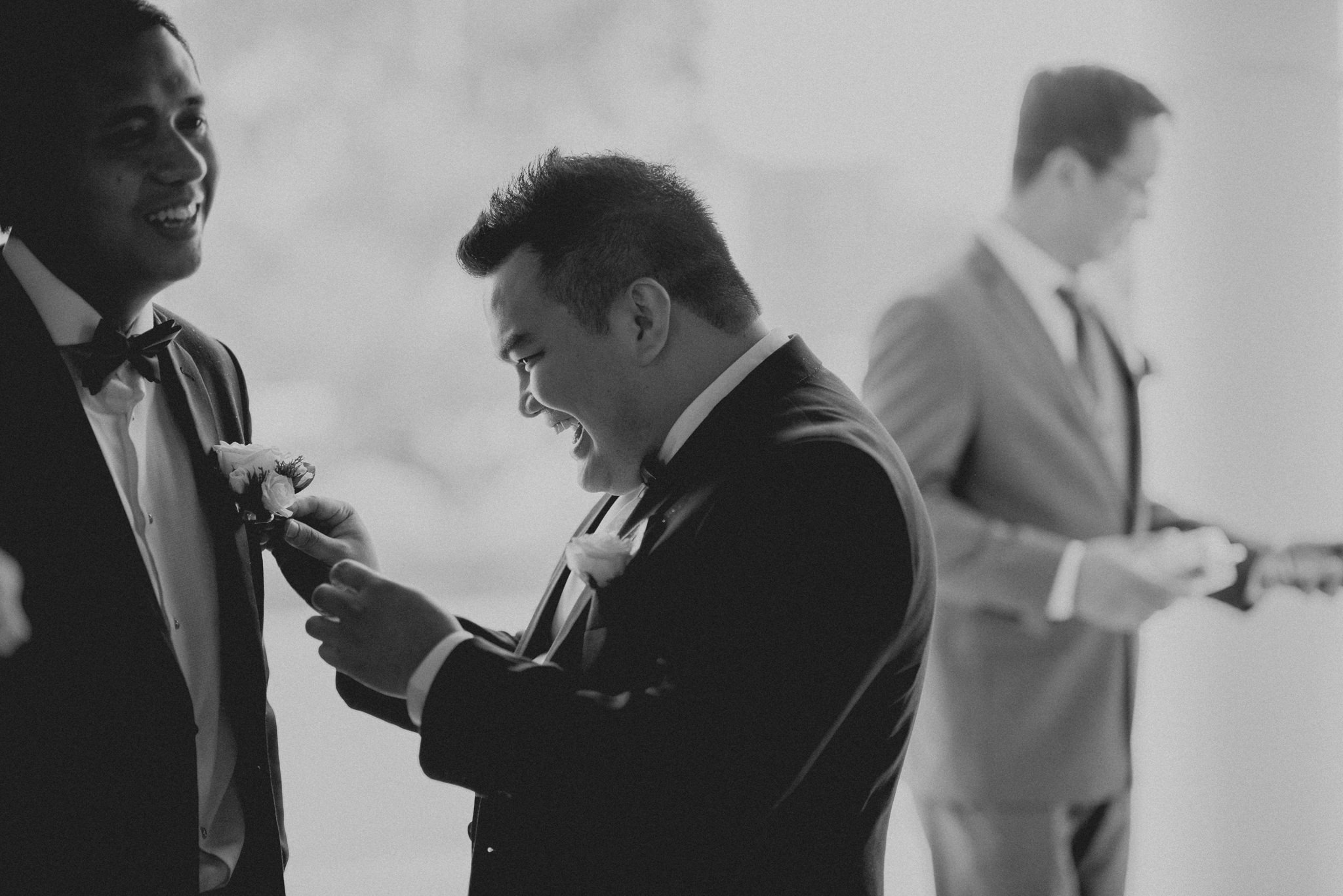 Groomsman laughs as he adjusts groom's boutineer