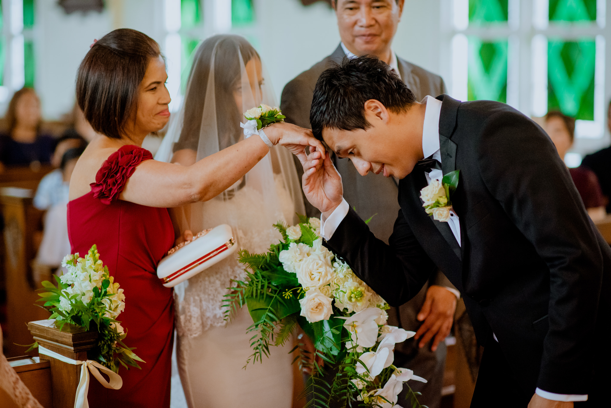 Groom greets mother of the bride by placing her hand on his forehead