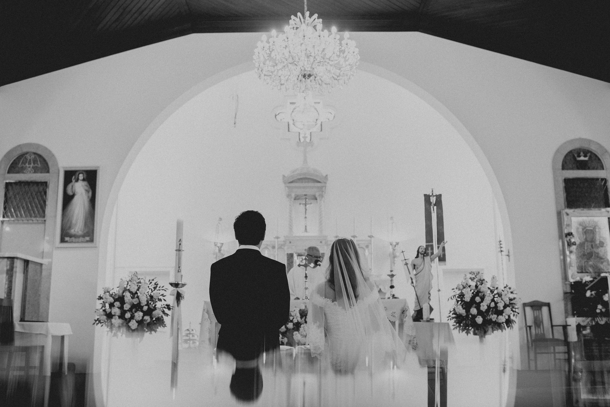 Bride and groom kneel in front of priest and altar at Catholic wedding ceremony