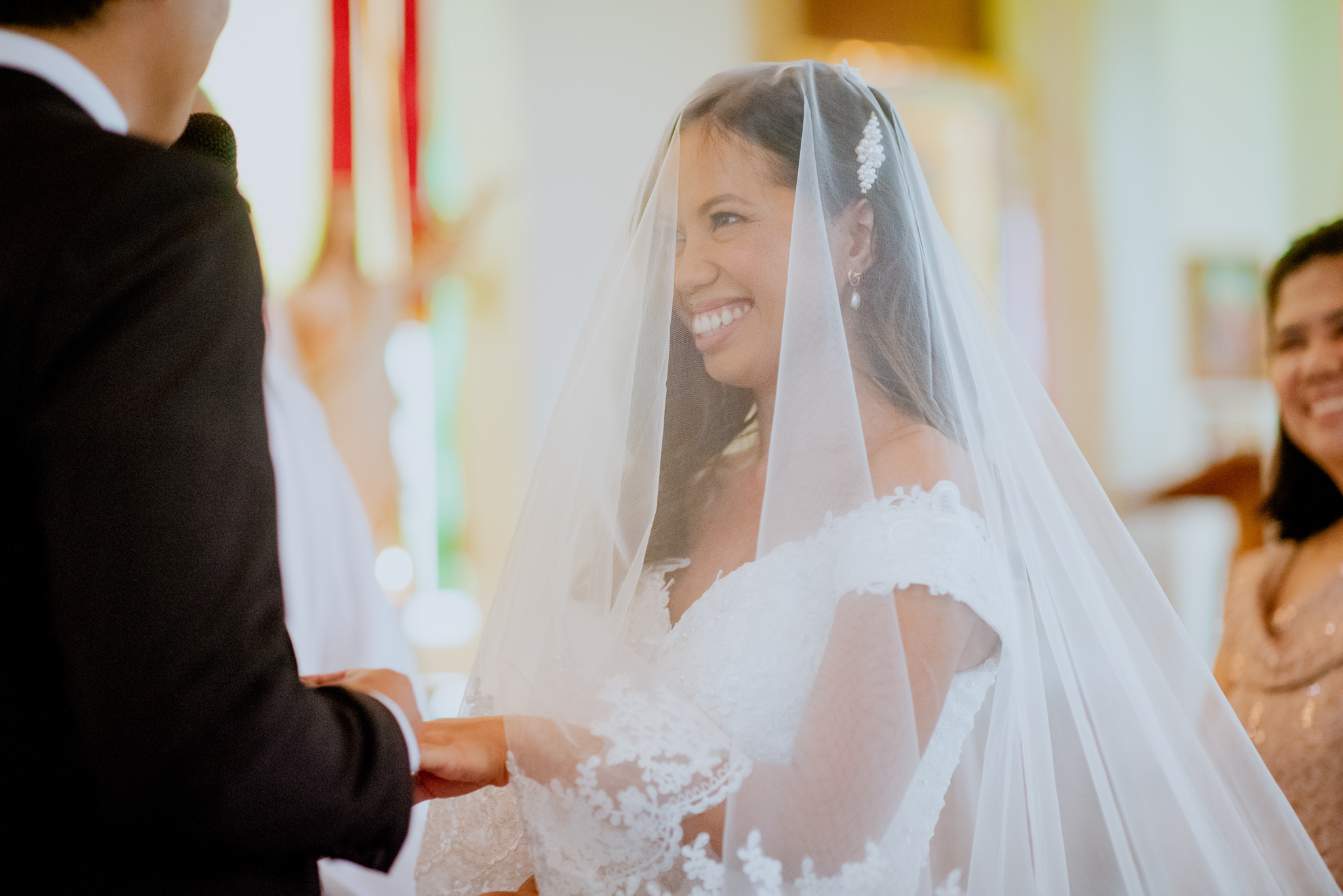 Bride laughs as she holds hands with her groom