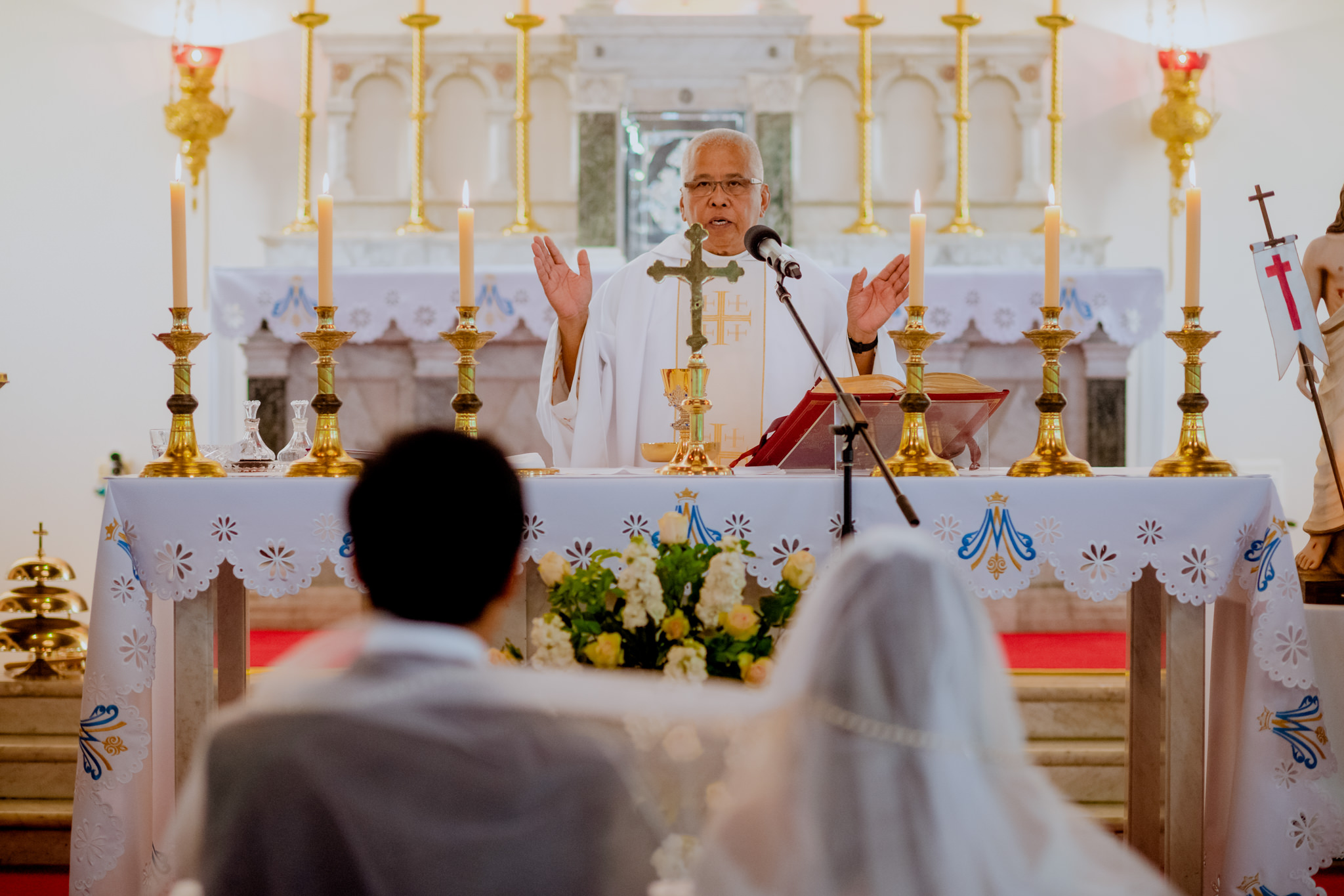 Catholic priest stretches his hands out as bride and groom kneel in front of him