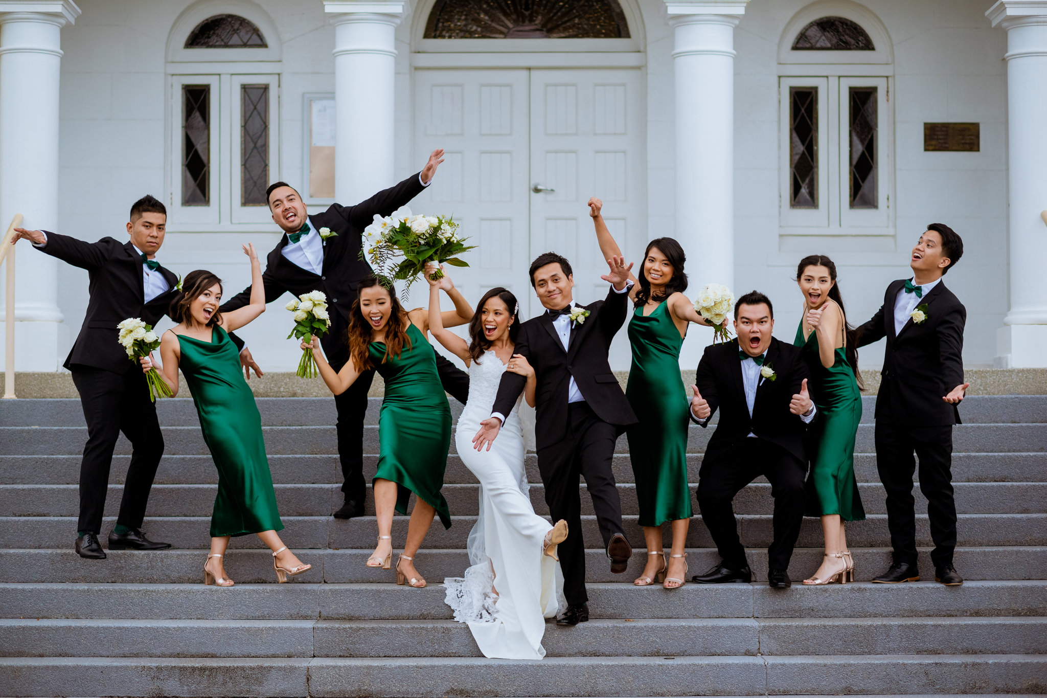 Bridal party having fun together on the steps of the church