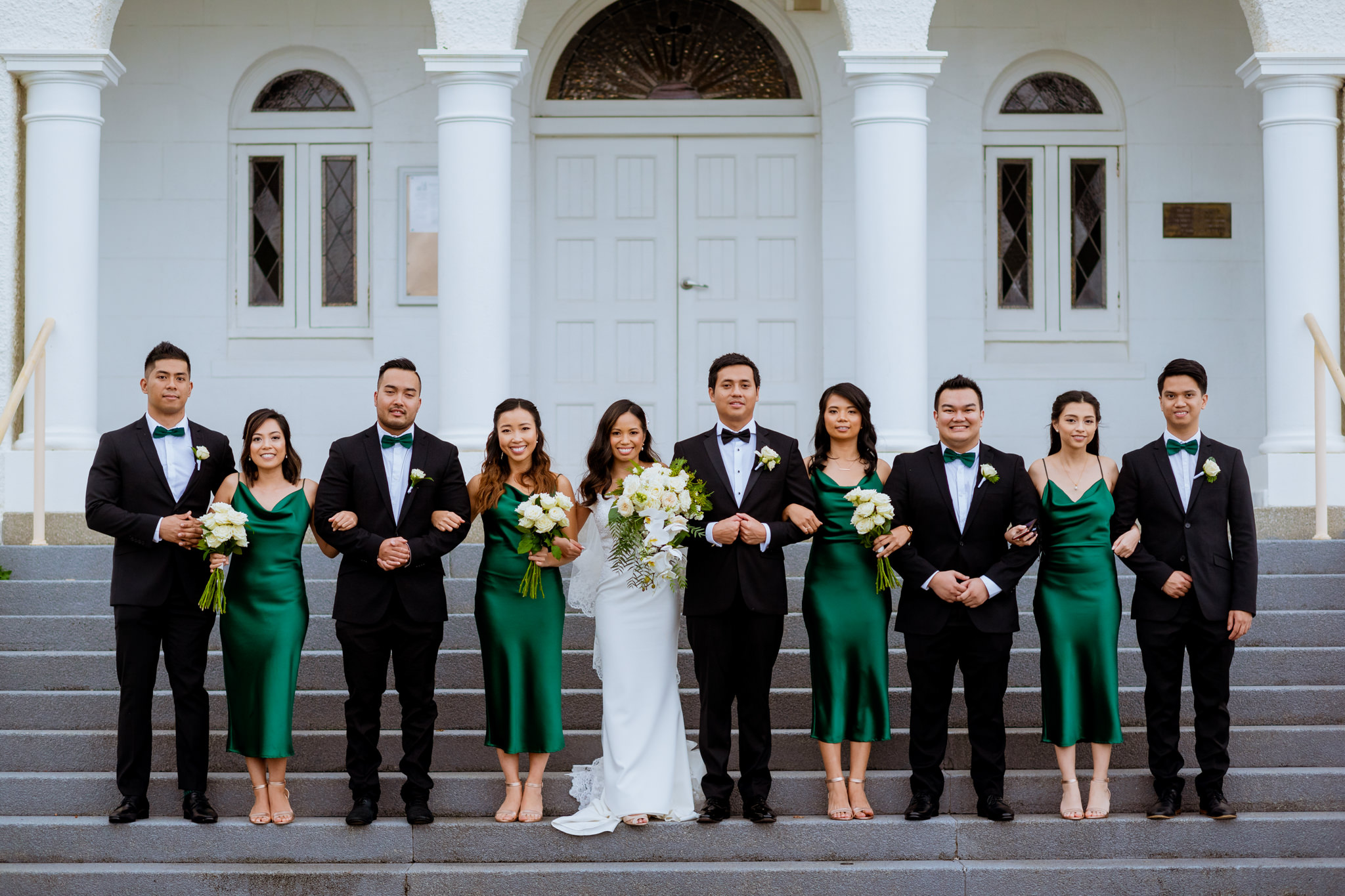Bridal party lined up with arms linked on the steps of a church