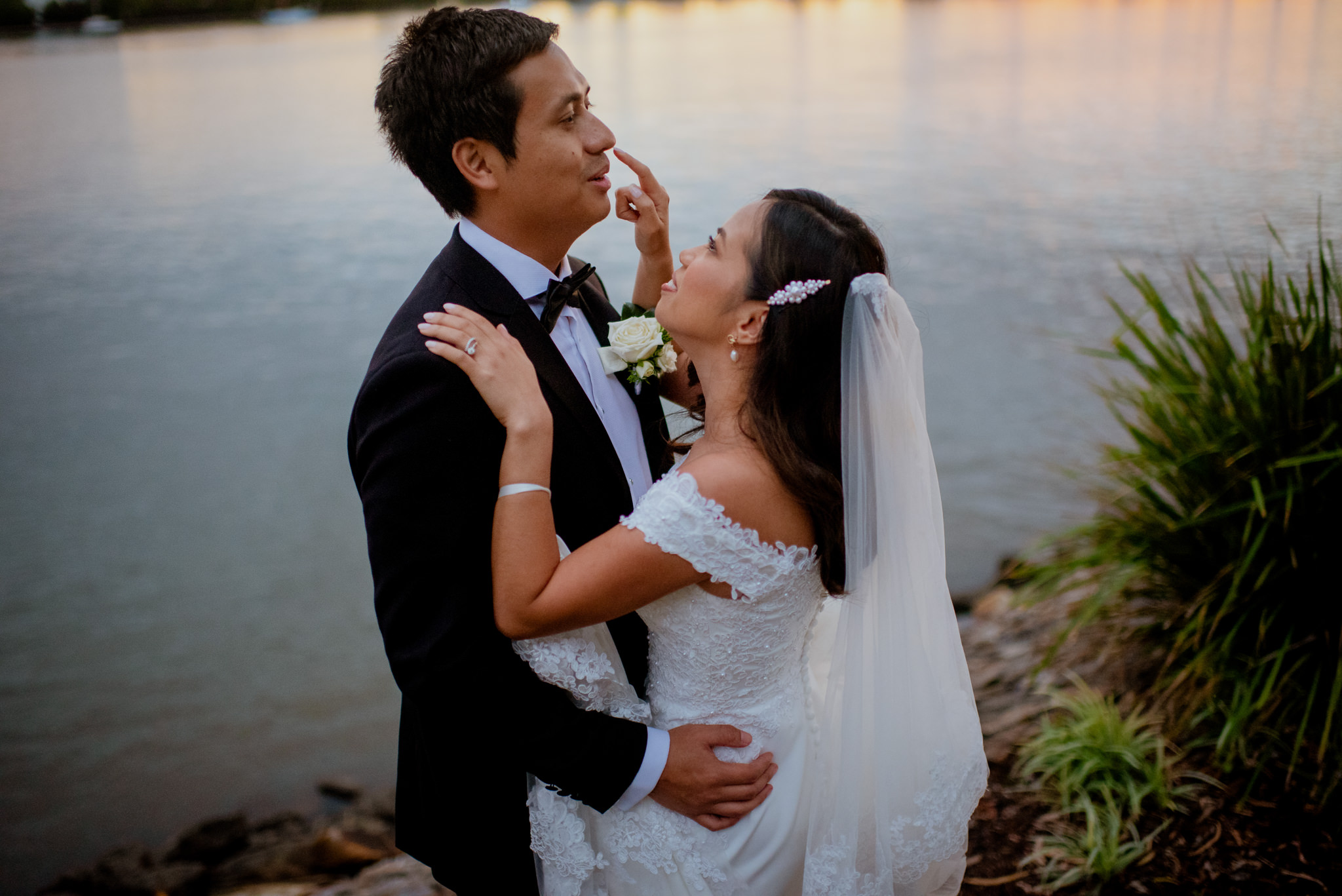 Bride playfully touches groom's nose whilst they hug on a riverbank