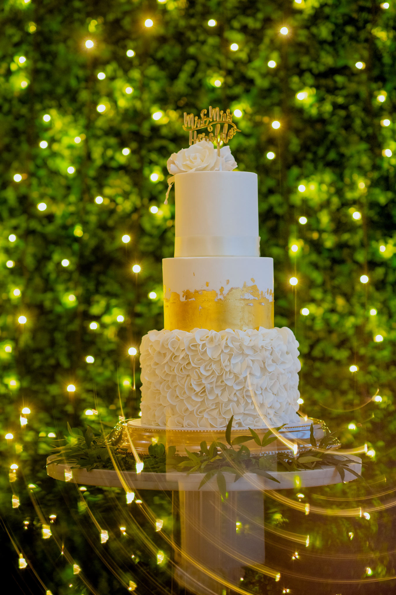 A three tiered white wedding cake in front of a green wall with fairy lights