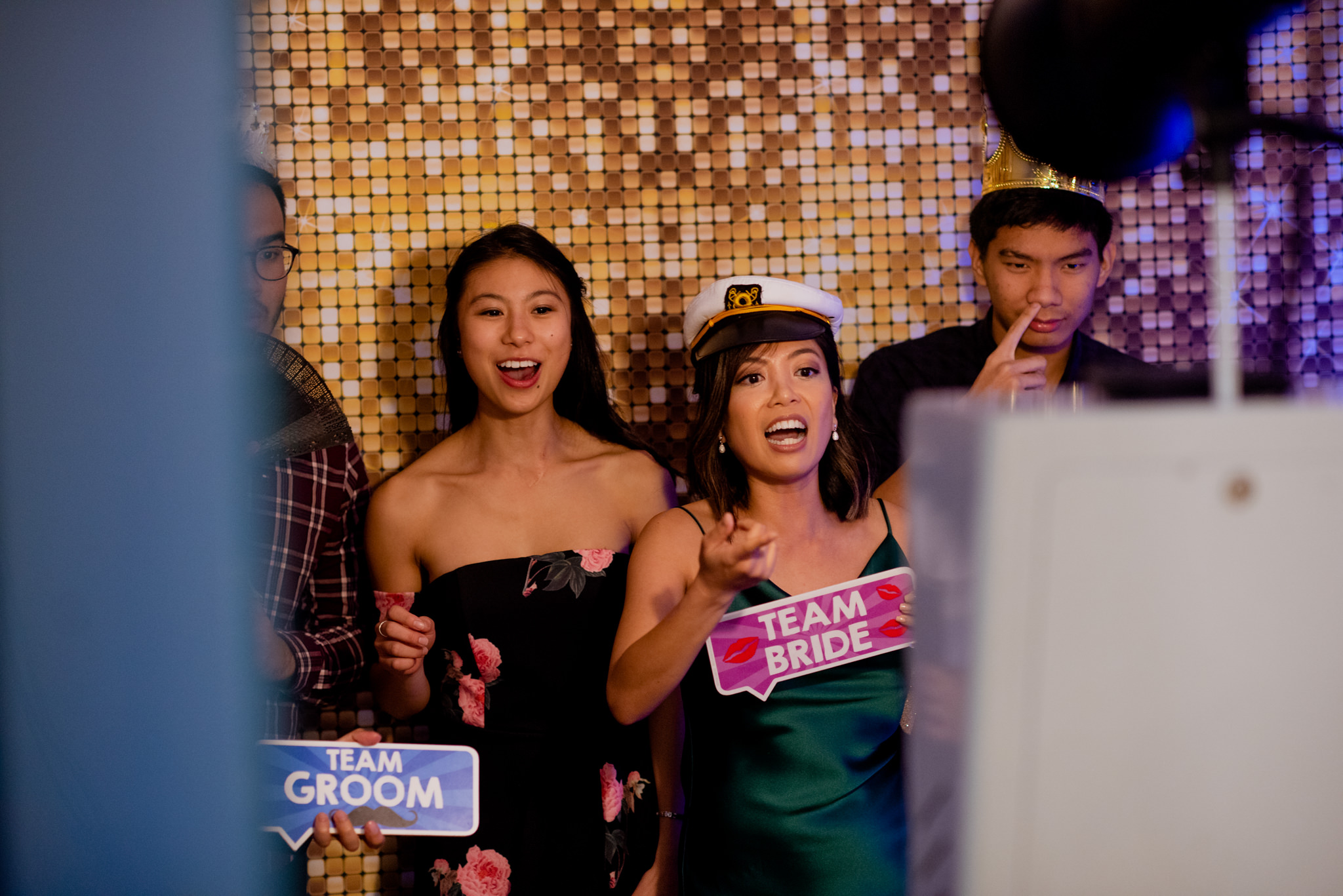 People using a photobooth with a bridesmaid wearing a captain's hat and holding up a sign