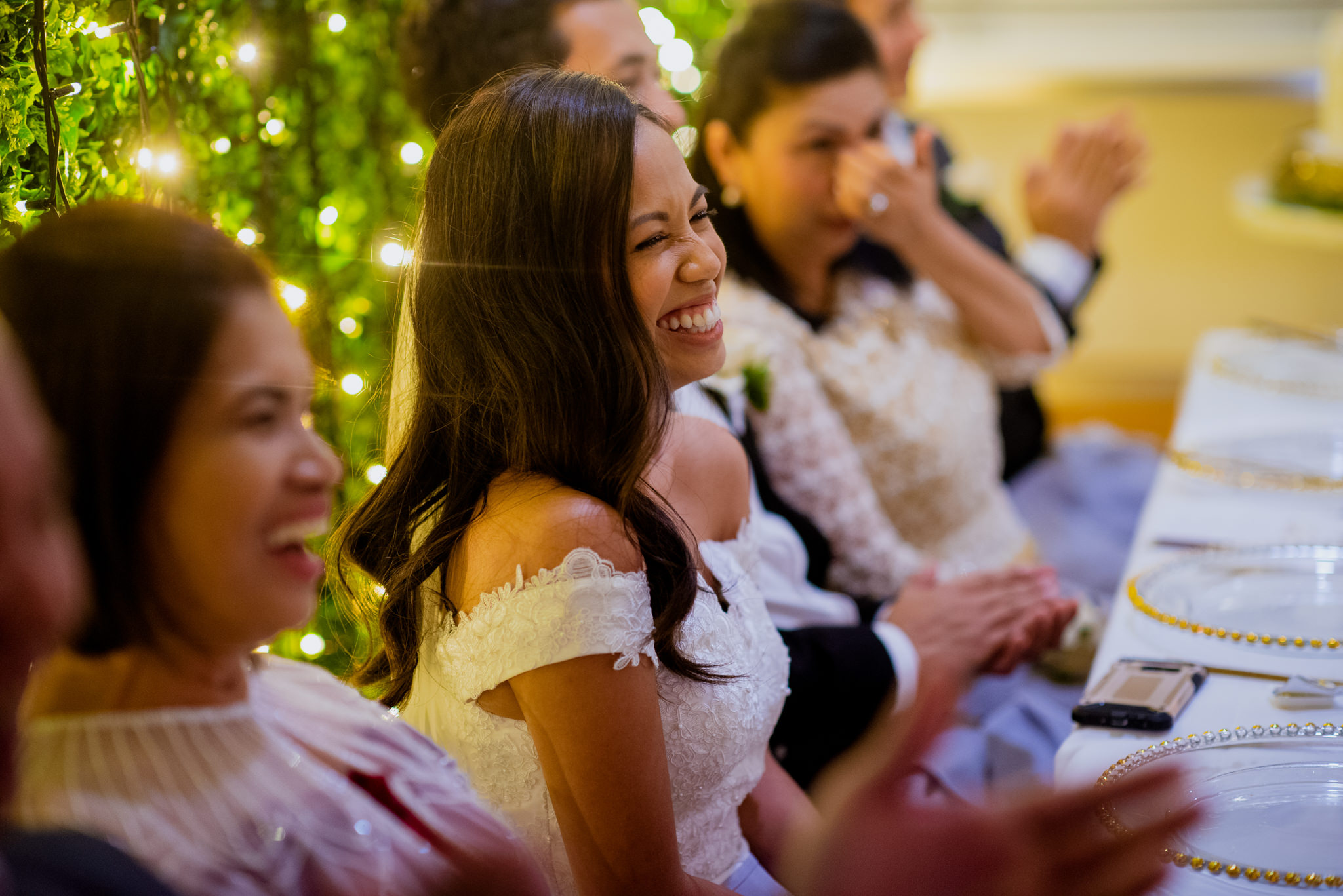Bride laughing whilst sitting next to her parents