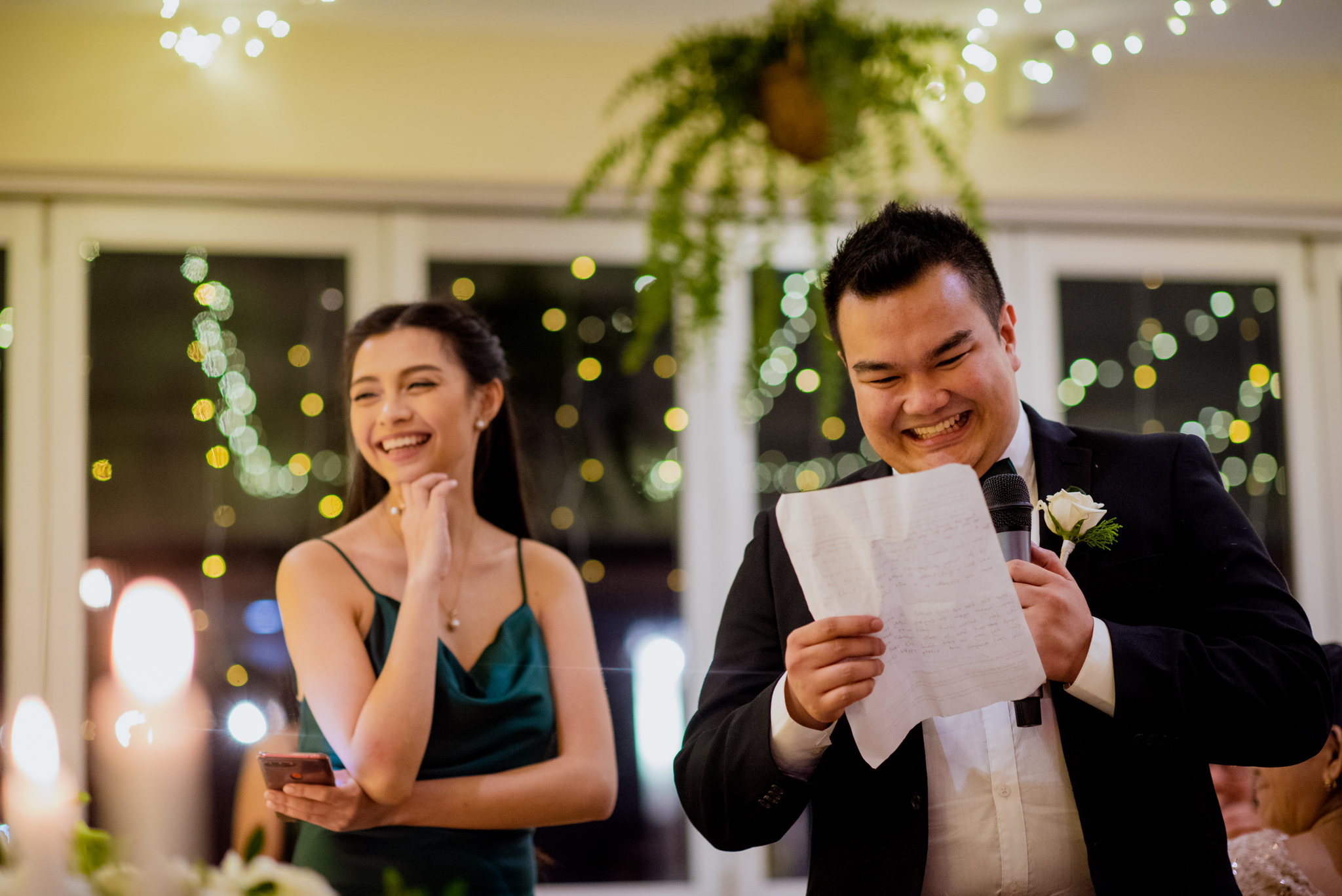 Best man laughing at his speech whilst bridesmaid looks on happily