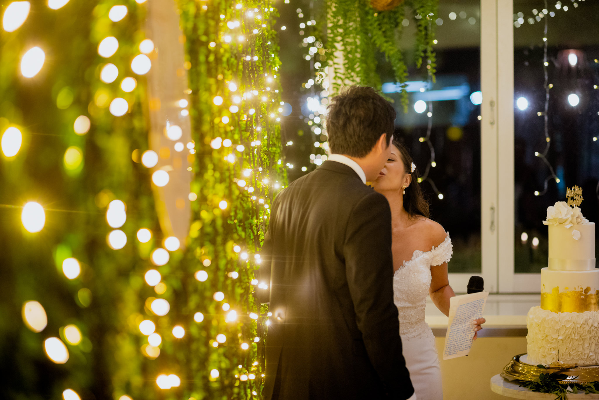 Bride and groom kissing in front of a wall of fairy lights at Northshore Harbour