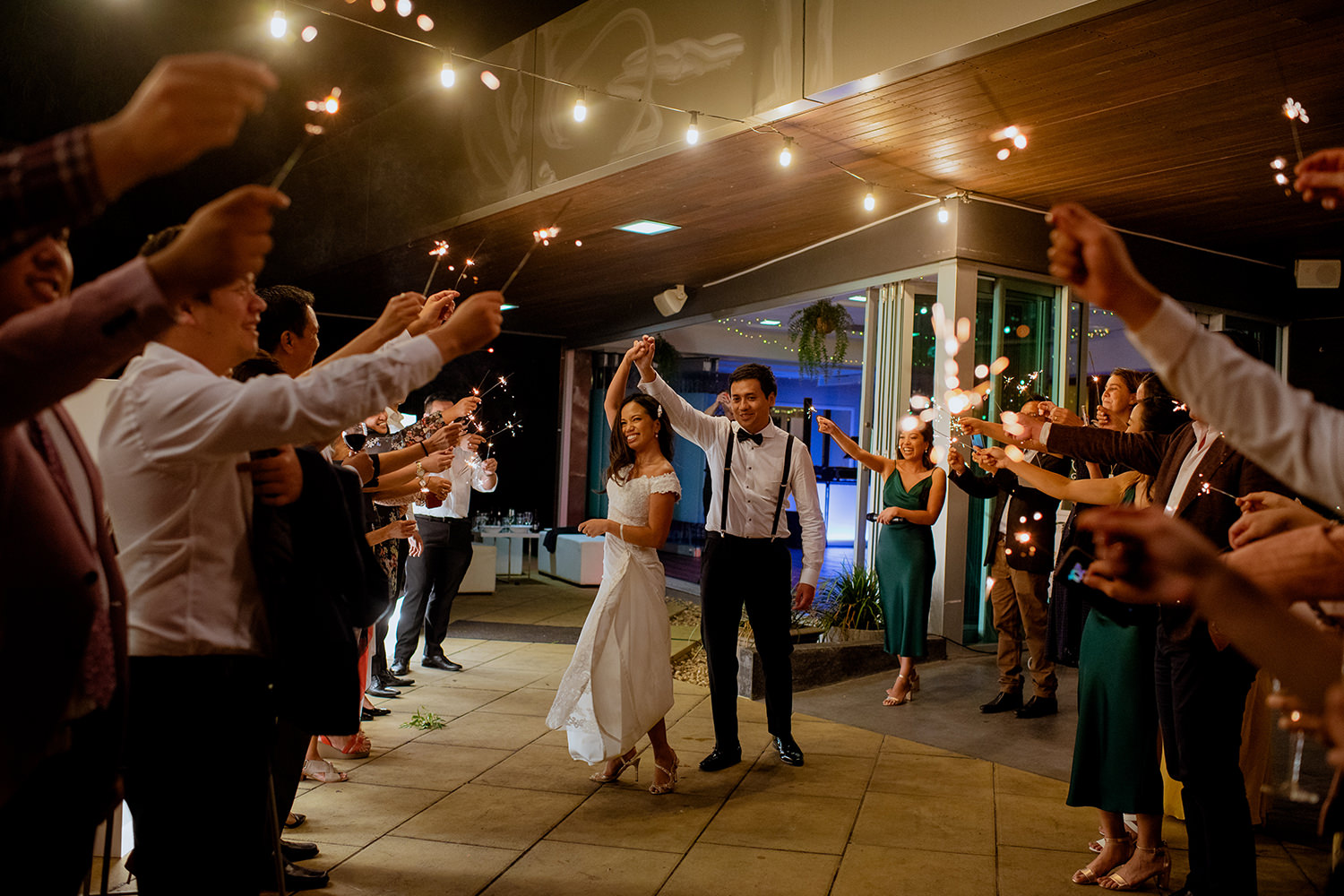 Groom dancing with his bride surrounded by guests with sparklers