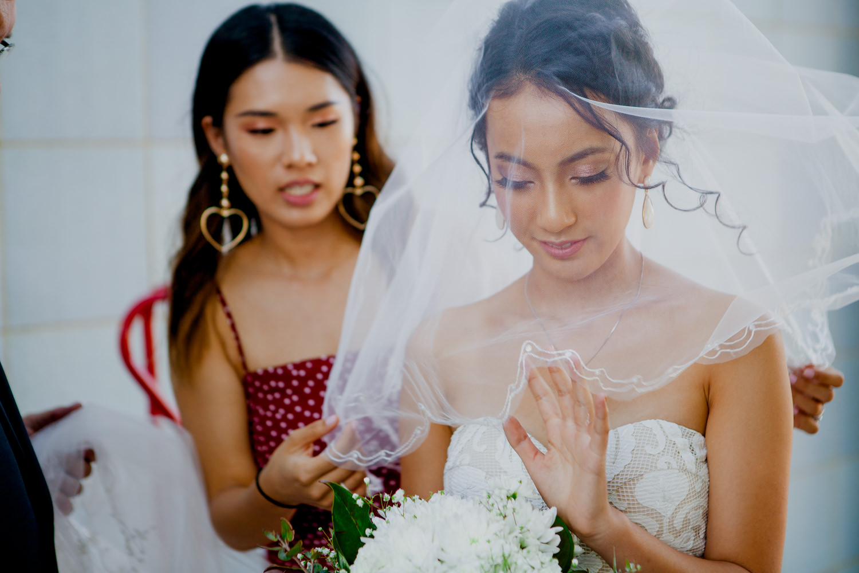 Asian bride adjusting her wedding veil