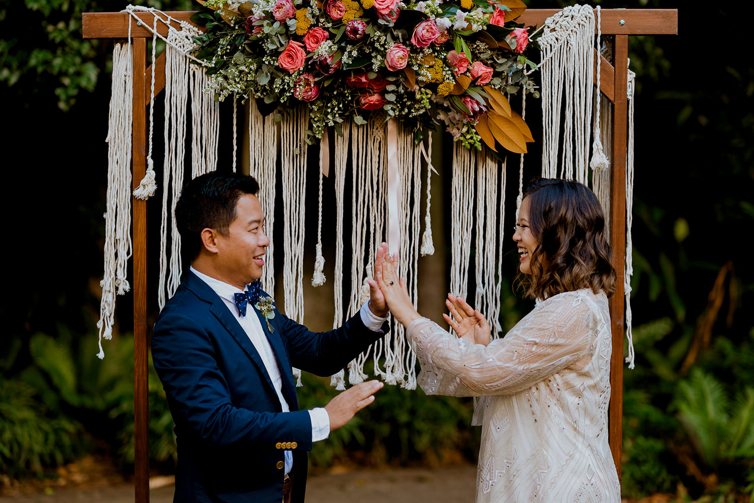 Playful asian bride and groom high-fiving in front of flower arbor