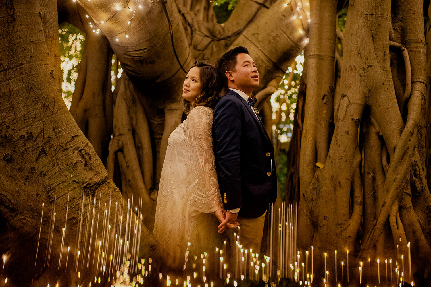 Asian couple hugging surrounded by fairy lights