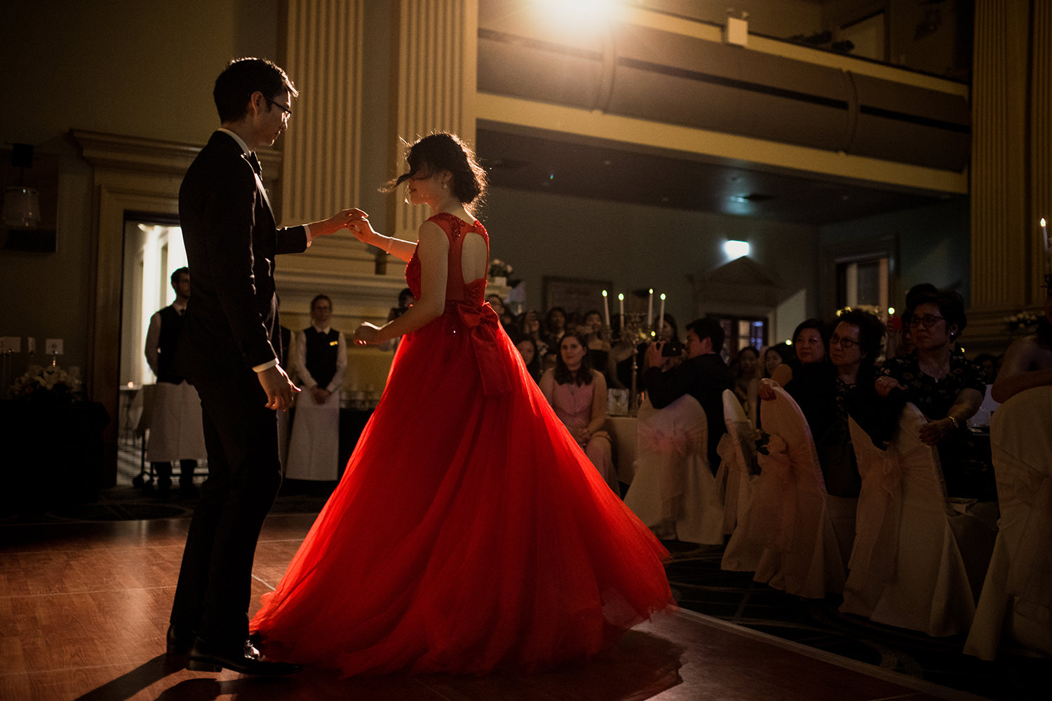 Bride in large red ballroom dress dancing with the groom