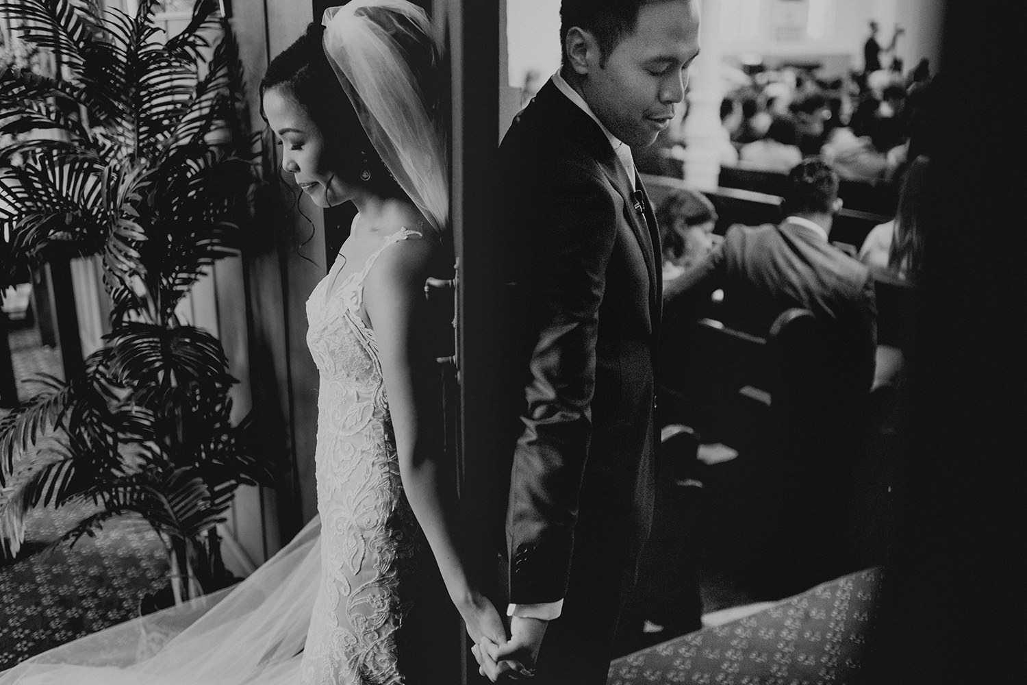 Asian bride and groom back-to-back praying together before their wedding