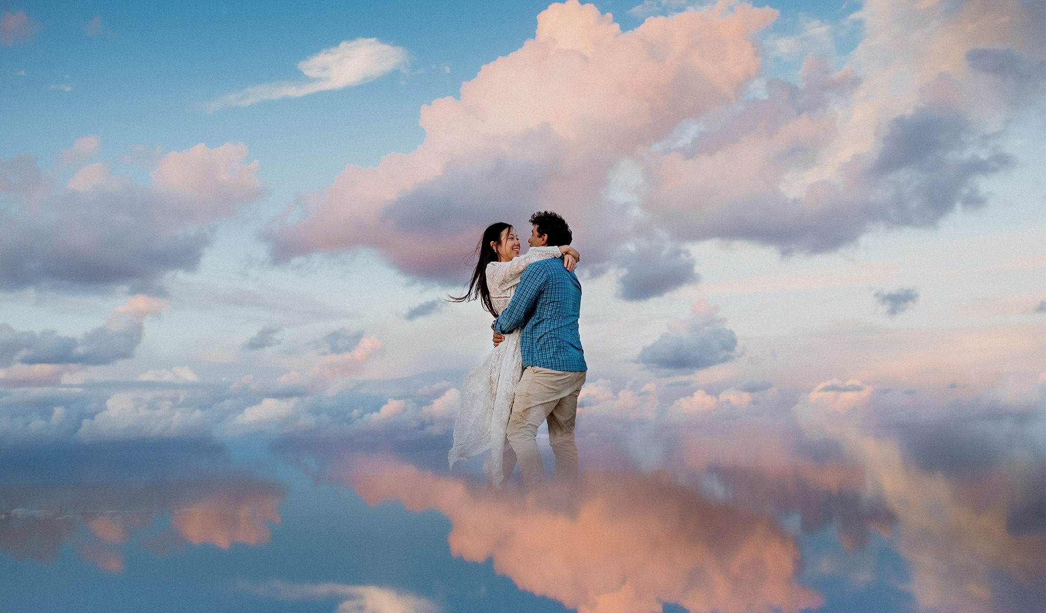 Interracial couple hugging with colourful sky reflected