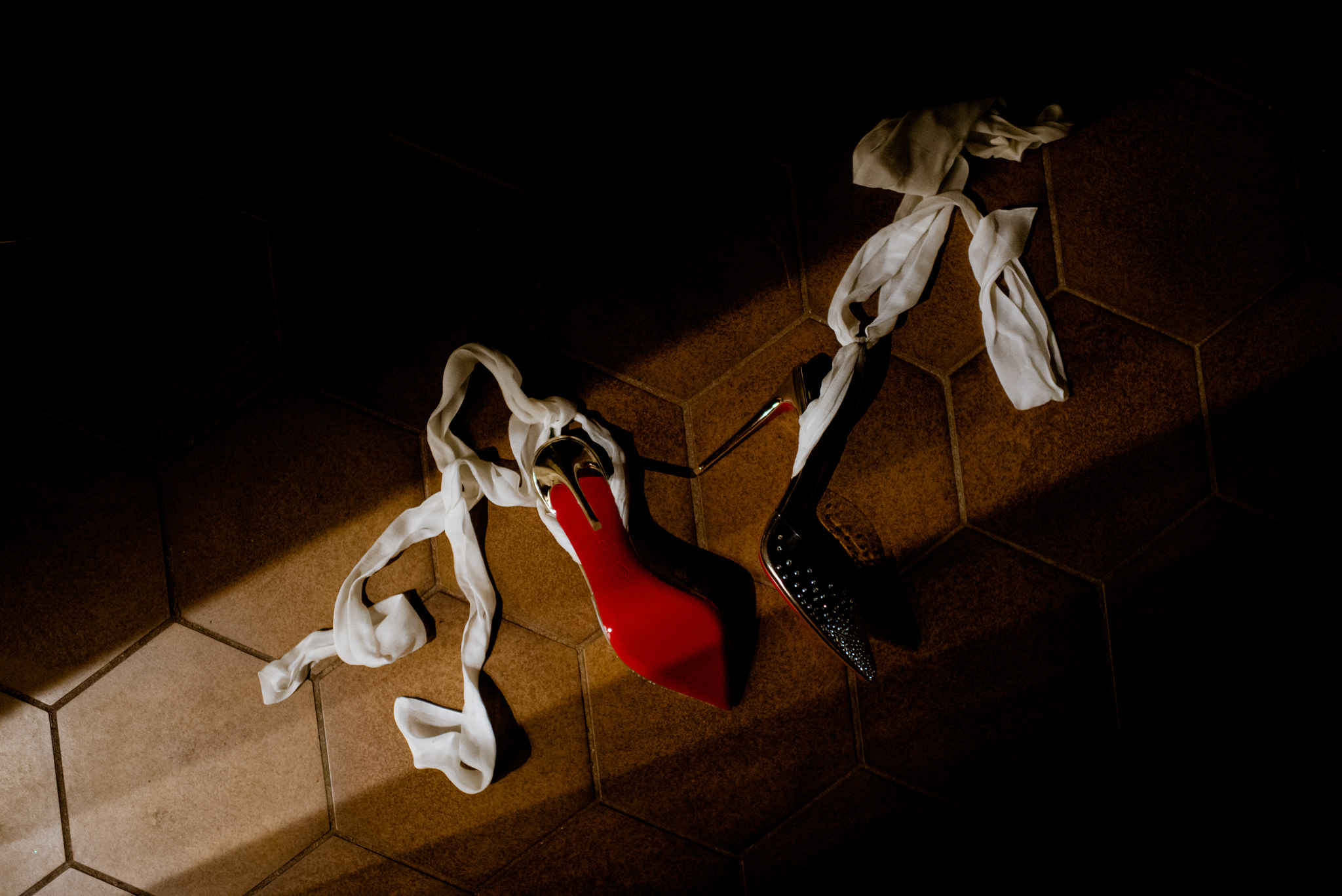 Red louboutin high heeled shoes lying on the floor in a slit of light.