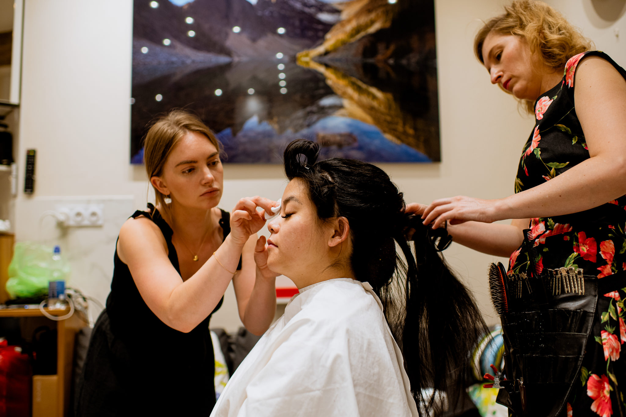 Bride-to-be sits as two women attend to her hair and make-up.