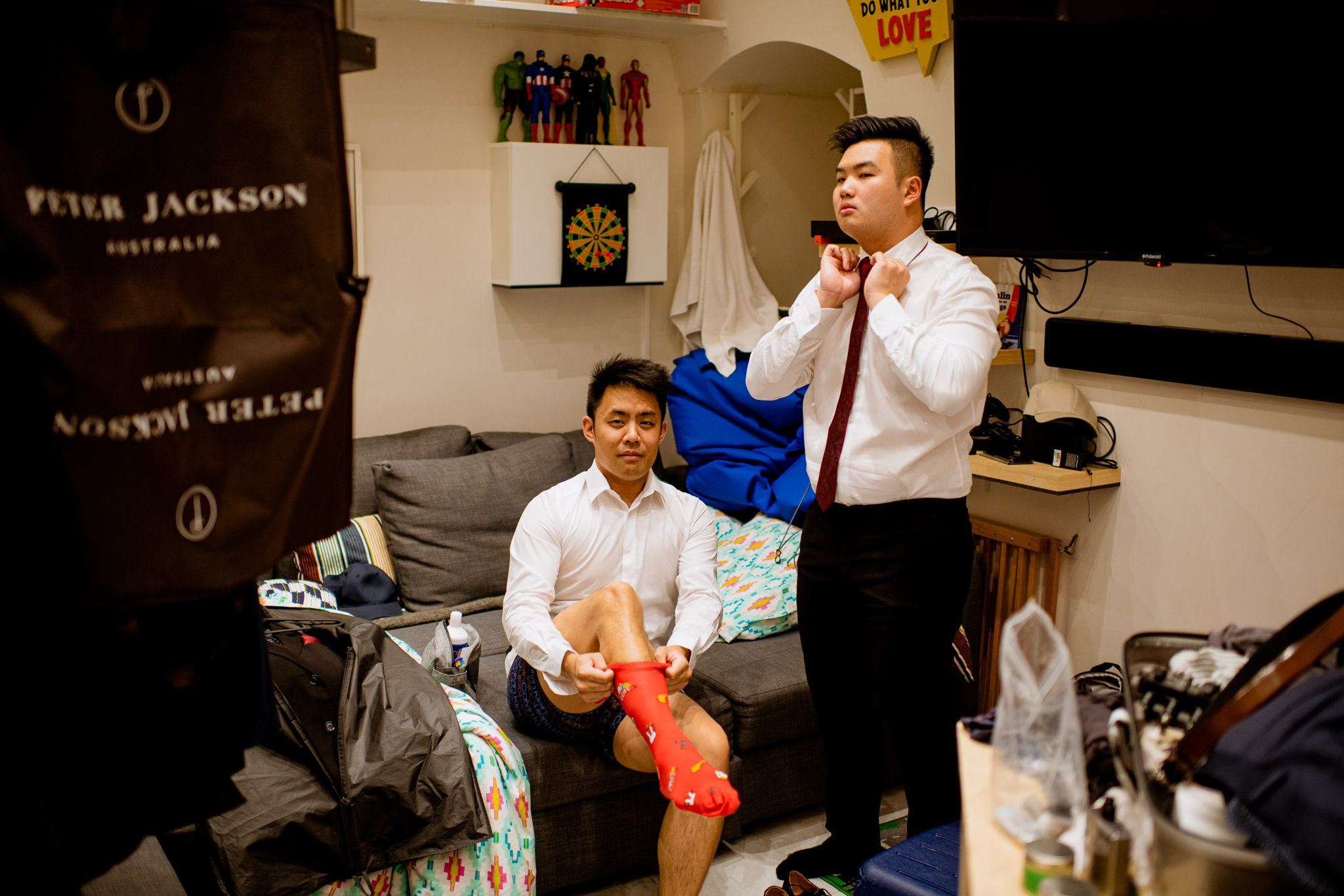 Two groomsmen get dressed in a messy room.