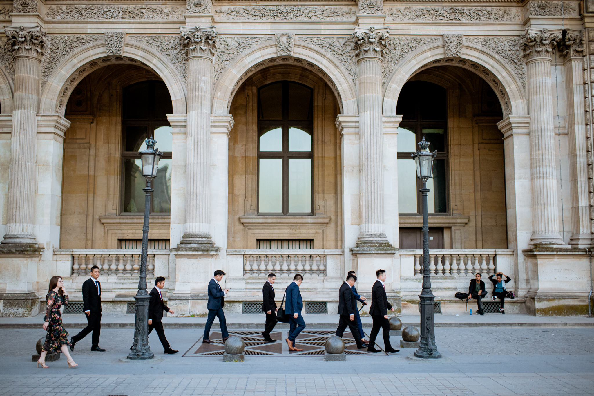 A wedding party walks in front of the Louvre archways.