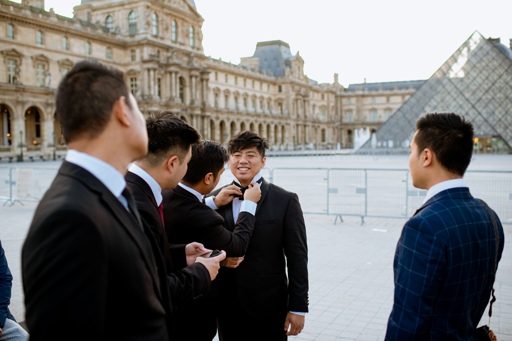Asian groom smiles as his groomsman ties his tie in front of the Louvre.