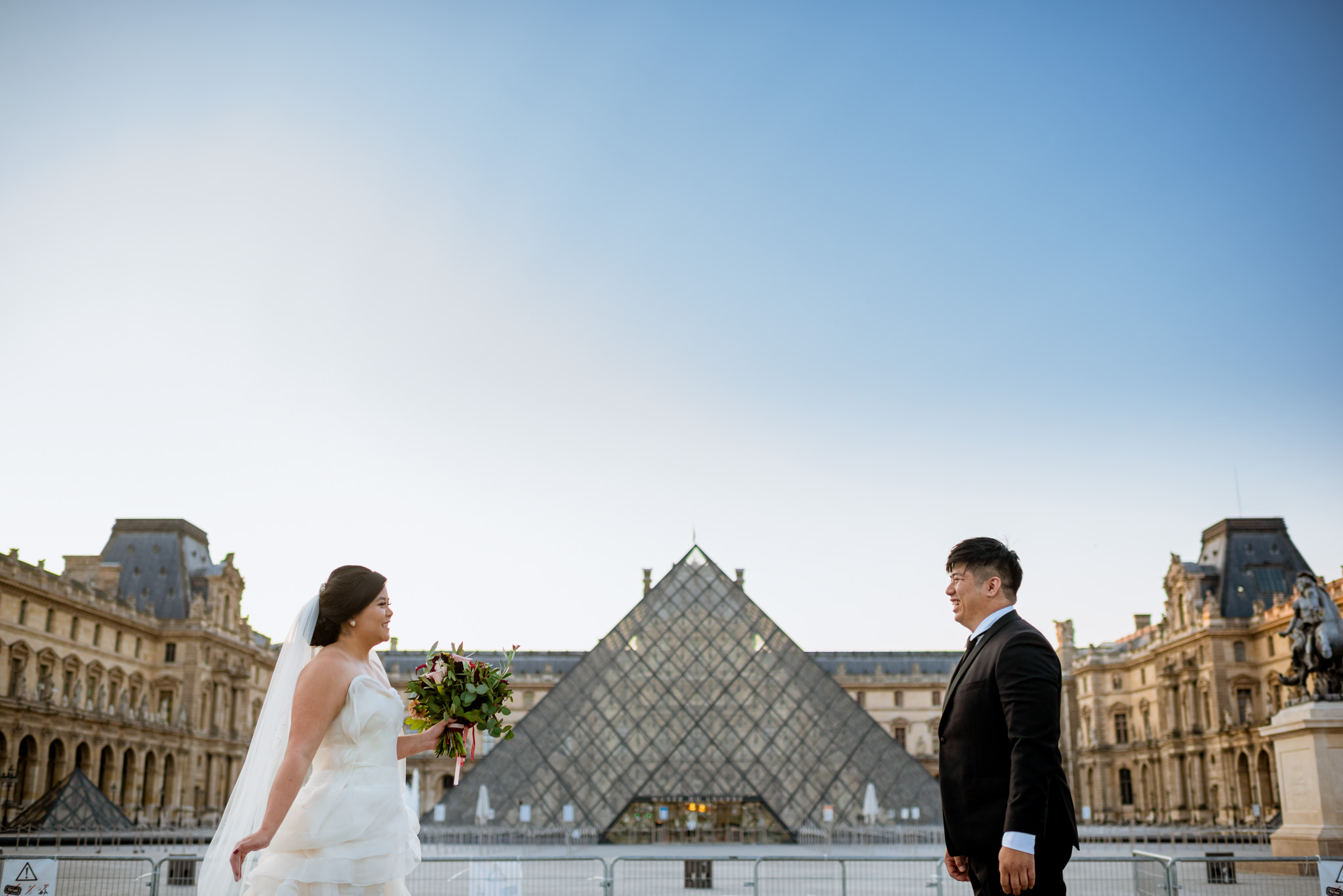 Bride and groom smile and face each other in front of the Louvre.