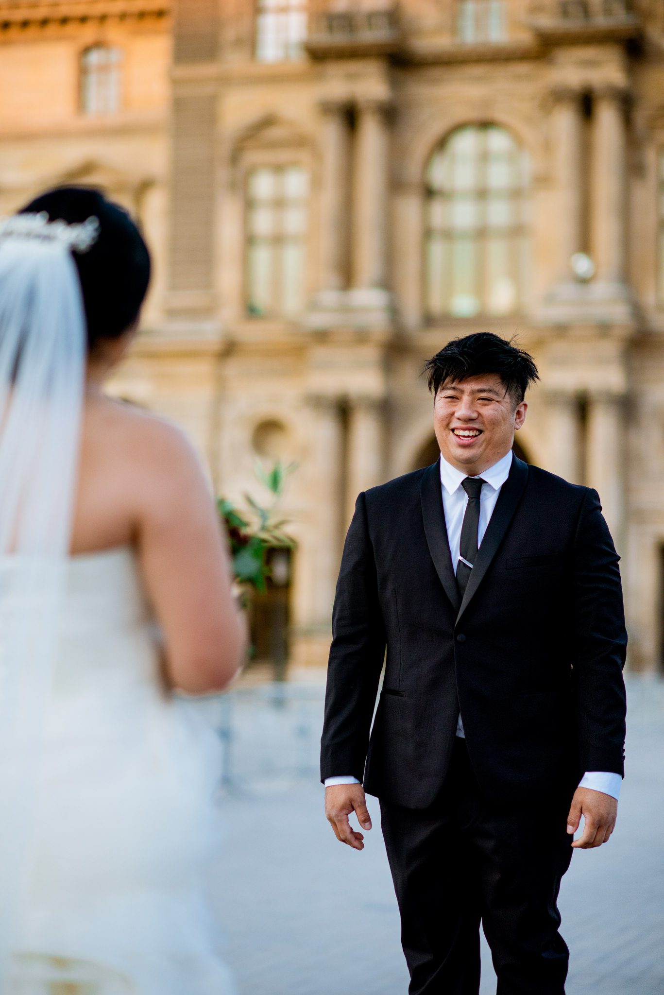 Asian groom laughs as he faces his bride.