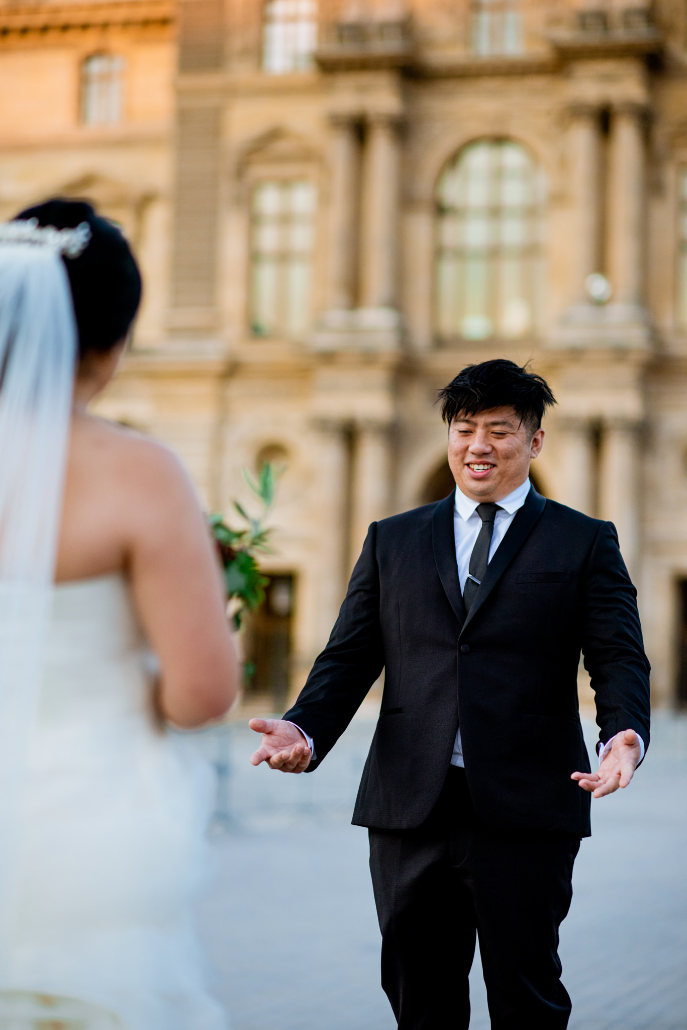 Asian groom gestures at his bride.