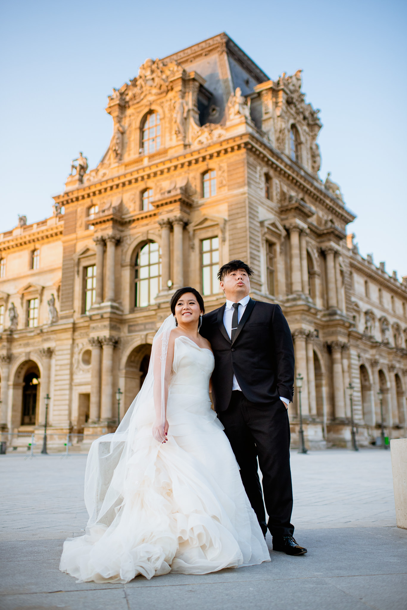 Asian bride and groom pose together in front of the Louvre.