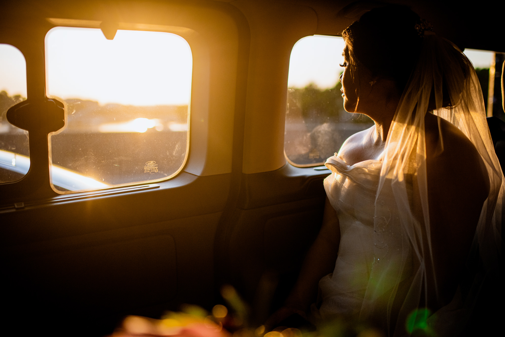Warm yellow glow of sunrise shines on bride as she faces out a taxi window.